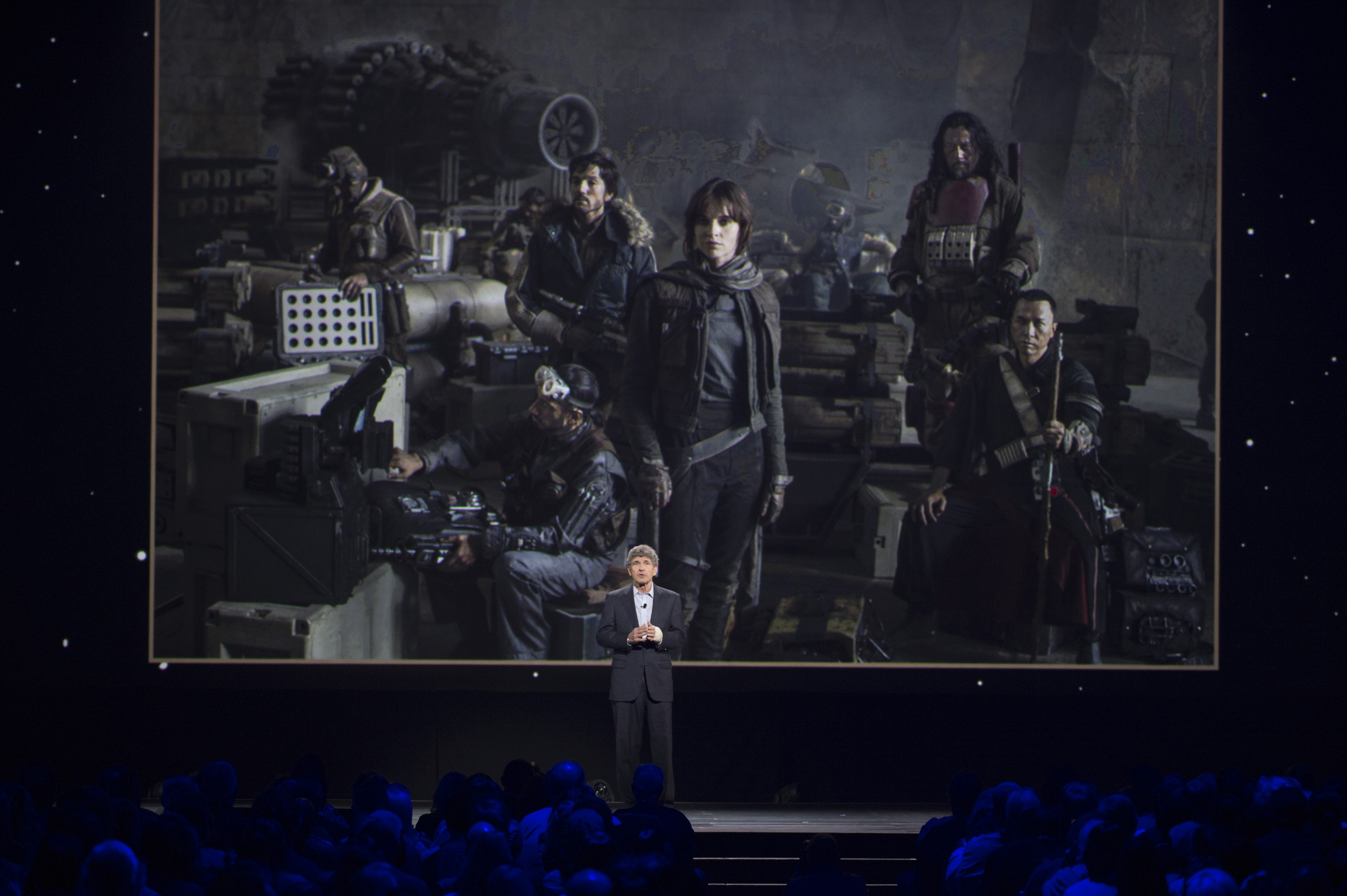 "Walt Disney Studios chairman Alan Horn stands in front of a picture of the cast of ""Rogue One: A Star Wars Story"" at Disney's D23 Expo in 2015."