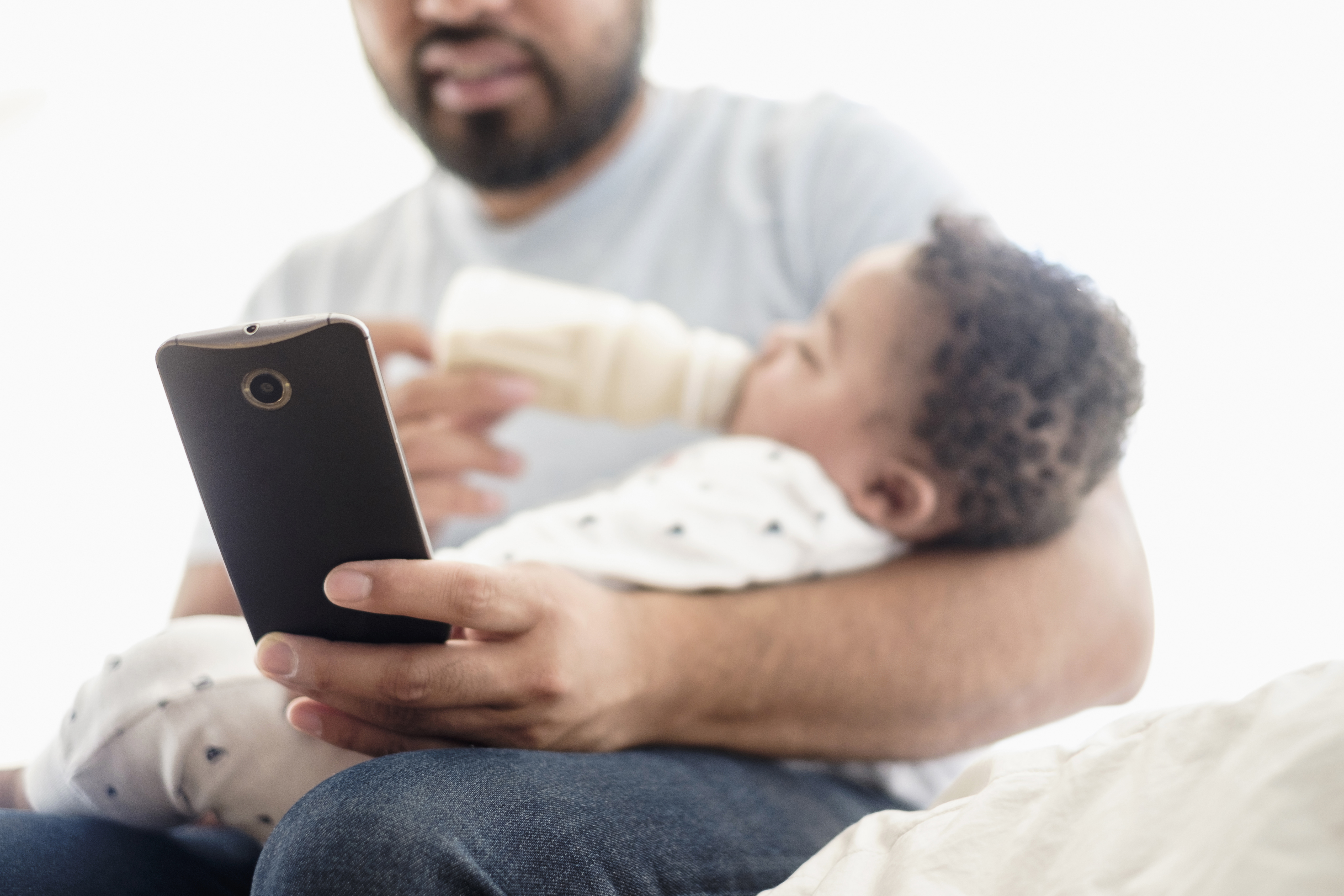 Father bottle feeding baby son and using cell phone