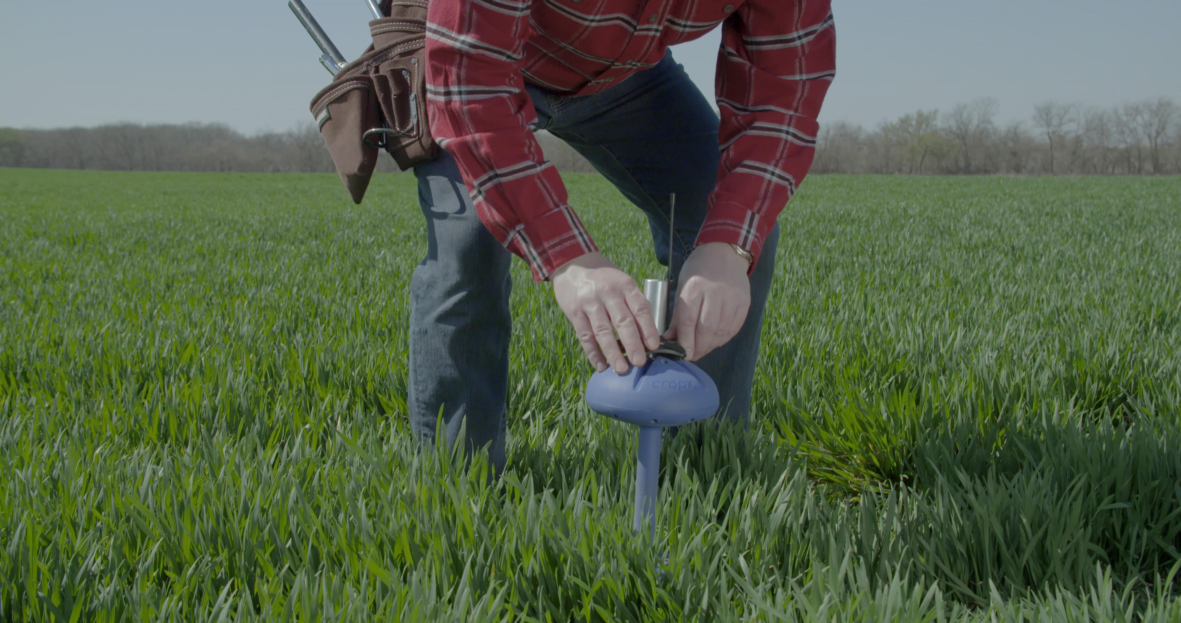 A farmer installs a CropX soil sensor device.
