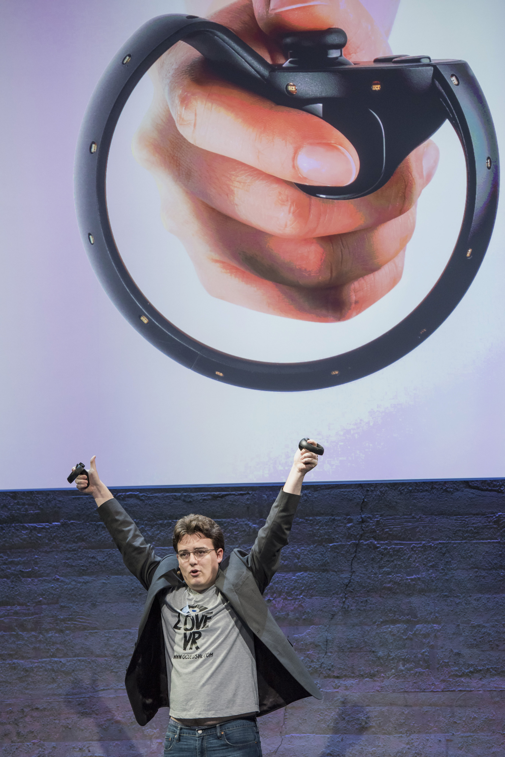 "Palmer Luckey, co-founder of Oculus VR. Inc. and creator of the Oculus Rift, holds up the Oculus Touch controller as he speaks during the Oculus VR Inc. ""Step Into The Rift"" event in San Francisco,   California, U.S., on Thursday, June 11, 2015. Facebook Inc.'s Oculus virtual-reality headsets will work with Microsoft Corp.'s Windows 10 and use the software maker's wireless Xbox game controller. Photographer: David Paul Morris/Bloomberg  *** Local Caption *** Palmer Luckey"