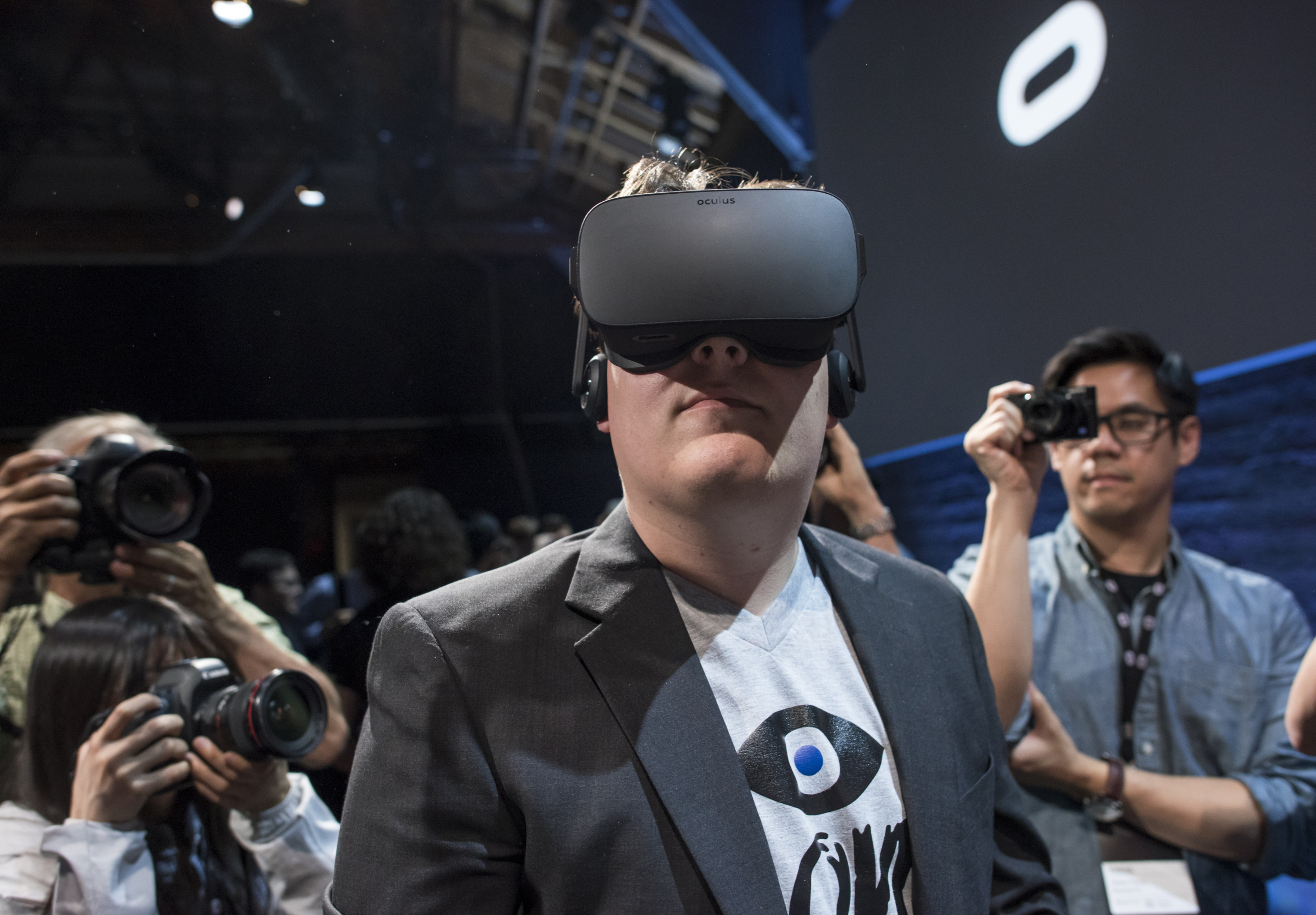 """Inc. and creator of the Oculus Rift, demonstrates the new Oculus Rift headset to the media during the Oculus VR Inc. """"Step Into The Rift"""" event in San Francisco, California, U.S., on Thursday, June 11, 2015. Facebook Inc.'s Oculus virtual-reality headsets will work with Microsoft Corp.'s Windows 10 and use the software maker's wireless Xbox game controller. Photographer: David Paul Morris/Bloomberg *** Local Caption *** Palmer Luckey"""