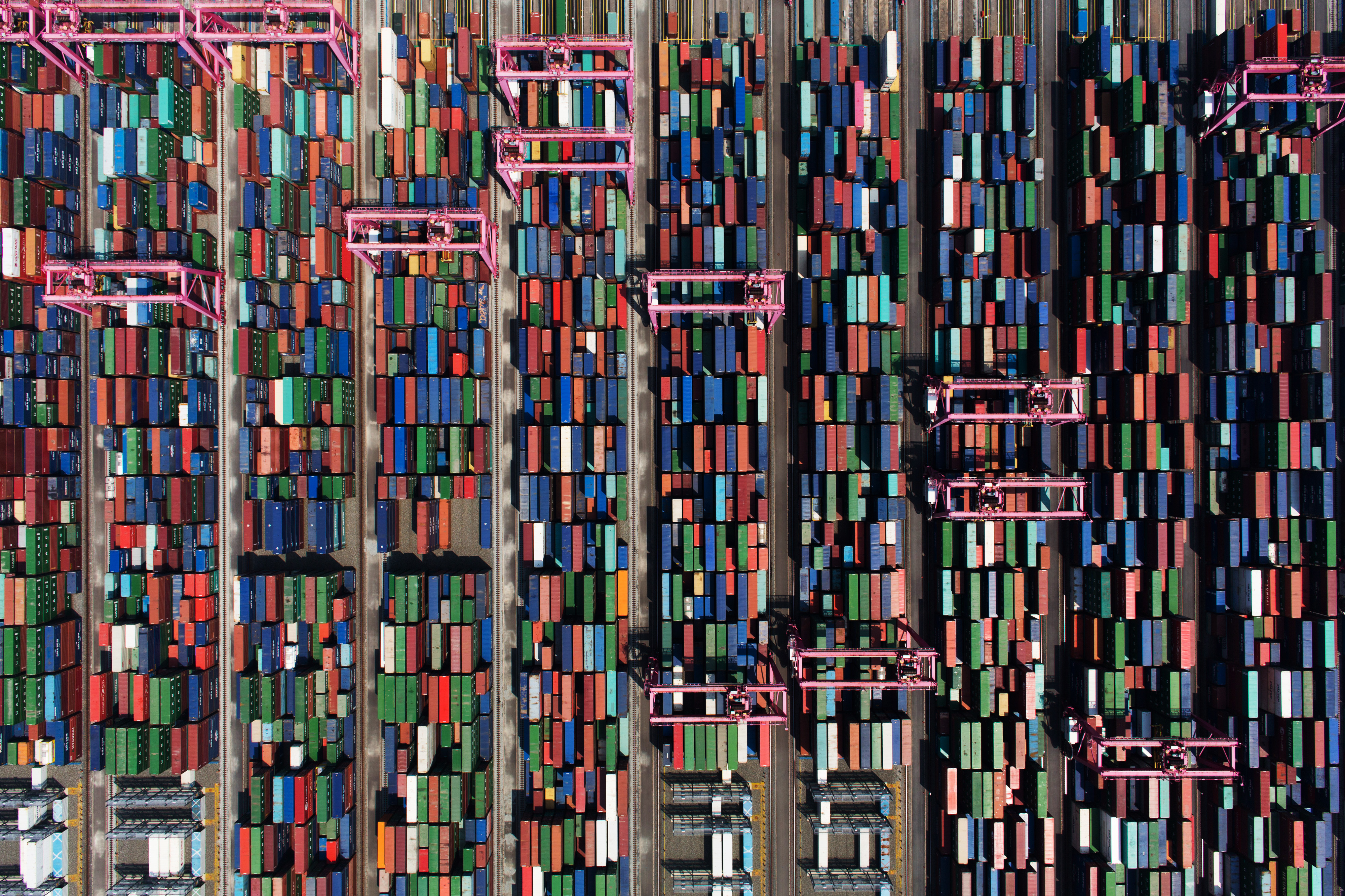 Shipping containers sit stacked among gantry cranes in this aerial photograph taken above the BNCT Co. container terminal at Busan New Port in Busan, South Korea, on Thursday, July 30, 2015. South Korea is scheduled to release trade figures on Aug. 1. Photographer: SeongJoon Cho/Bloomberg via Getty Images
