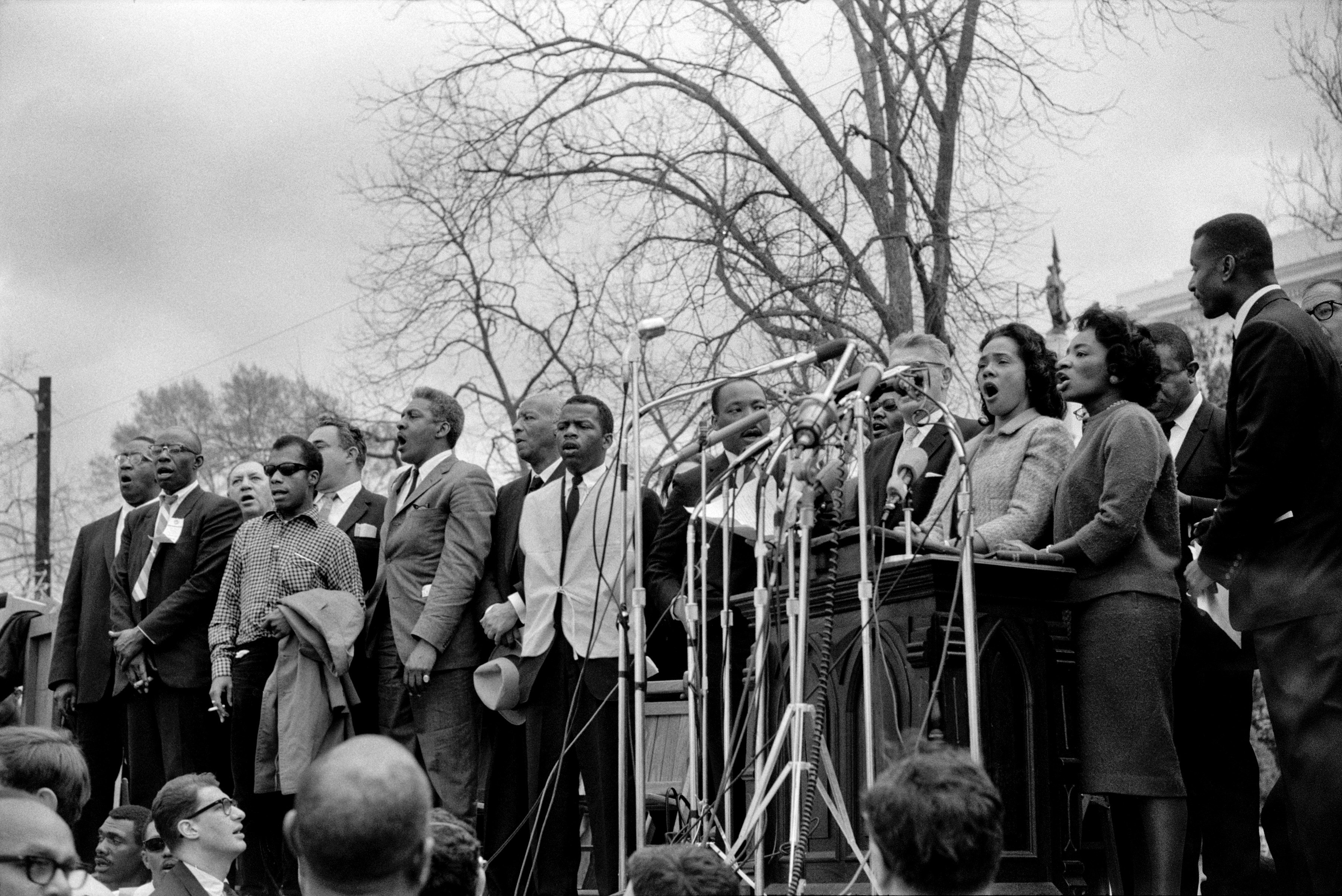 Civil rights and Union leaders sing 'We Shall Overcome' at the conclusion of the Selma to Montgomery civil rights march on March 25, 1965 in Montgomery, Alabama.