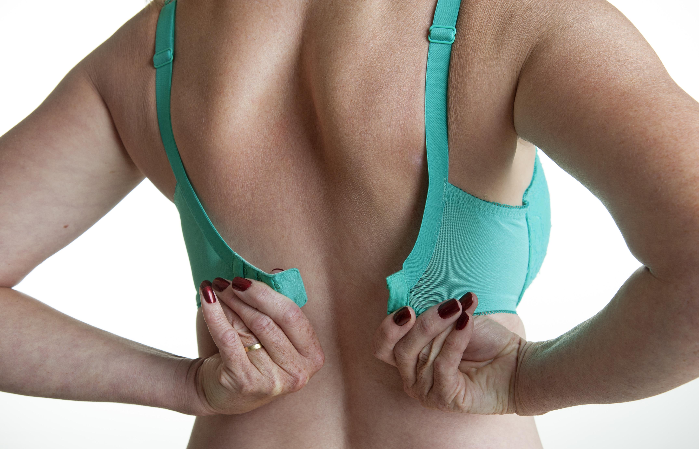 Woman fastening a green bra