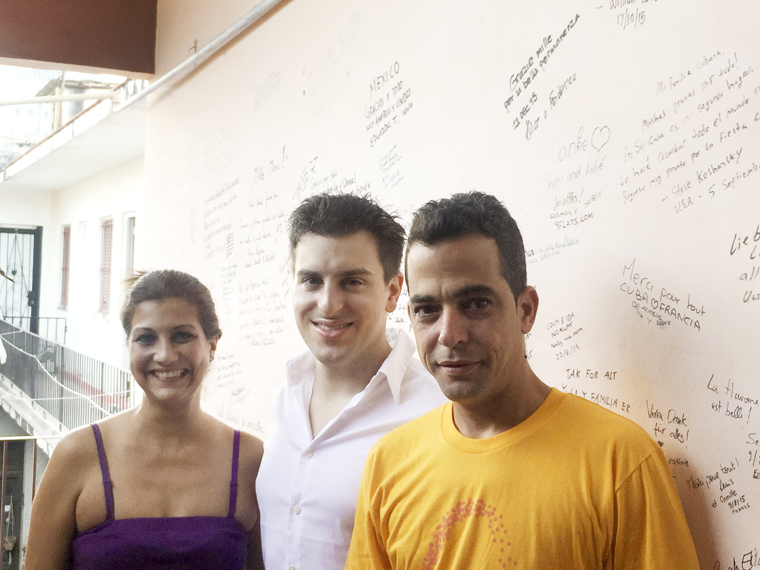 Airbnb CEO Brian Chesky (center) with a Havana host couple, in front of a wall festooned with signed notes from their Airbnb guests.