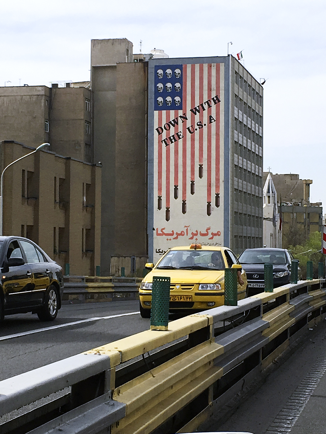 """A revolutionary mural in Tehran shows bombs and skulls on the US flag, with the words, """"We will not compromise with America, even for one second."""" The decades-old mural has remained, despite Iran's nuclear deal with the West."""