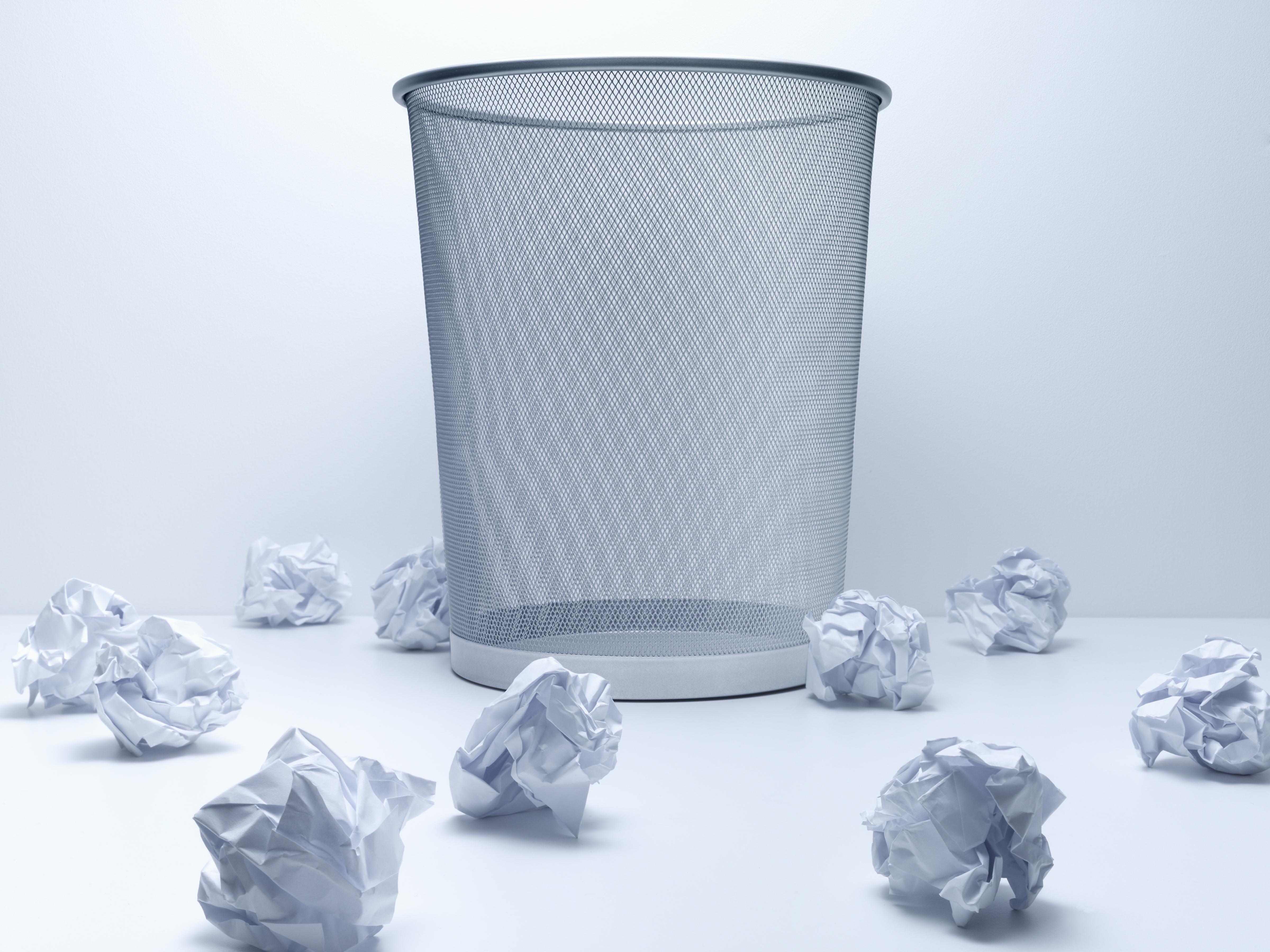 Crumpled balls of paper beside wastebasket
