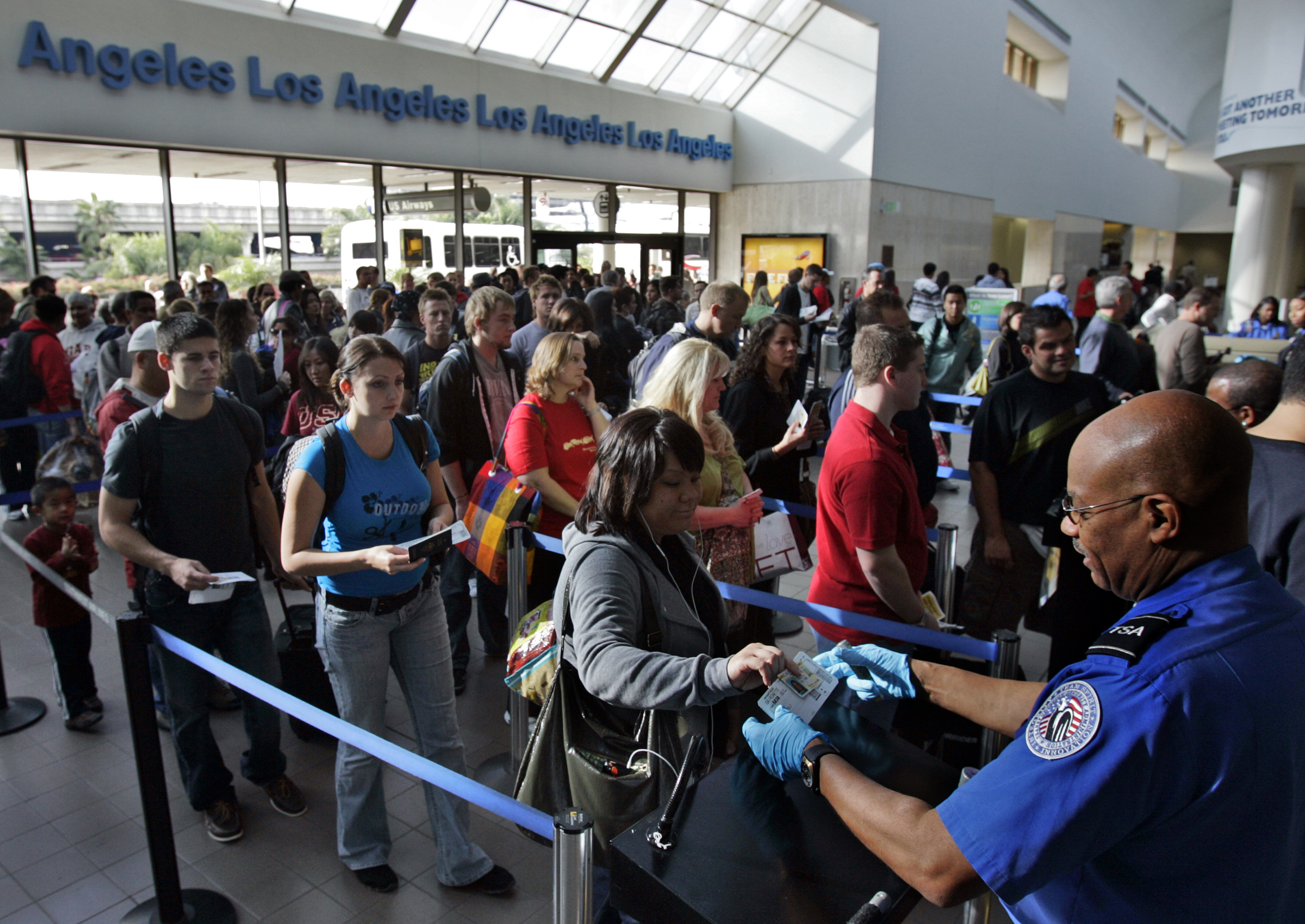 Travelers form a long security check line that is extended out of departure lounge at Los Angeles a
