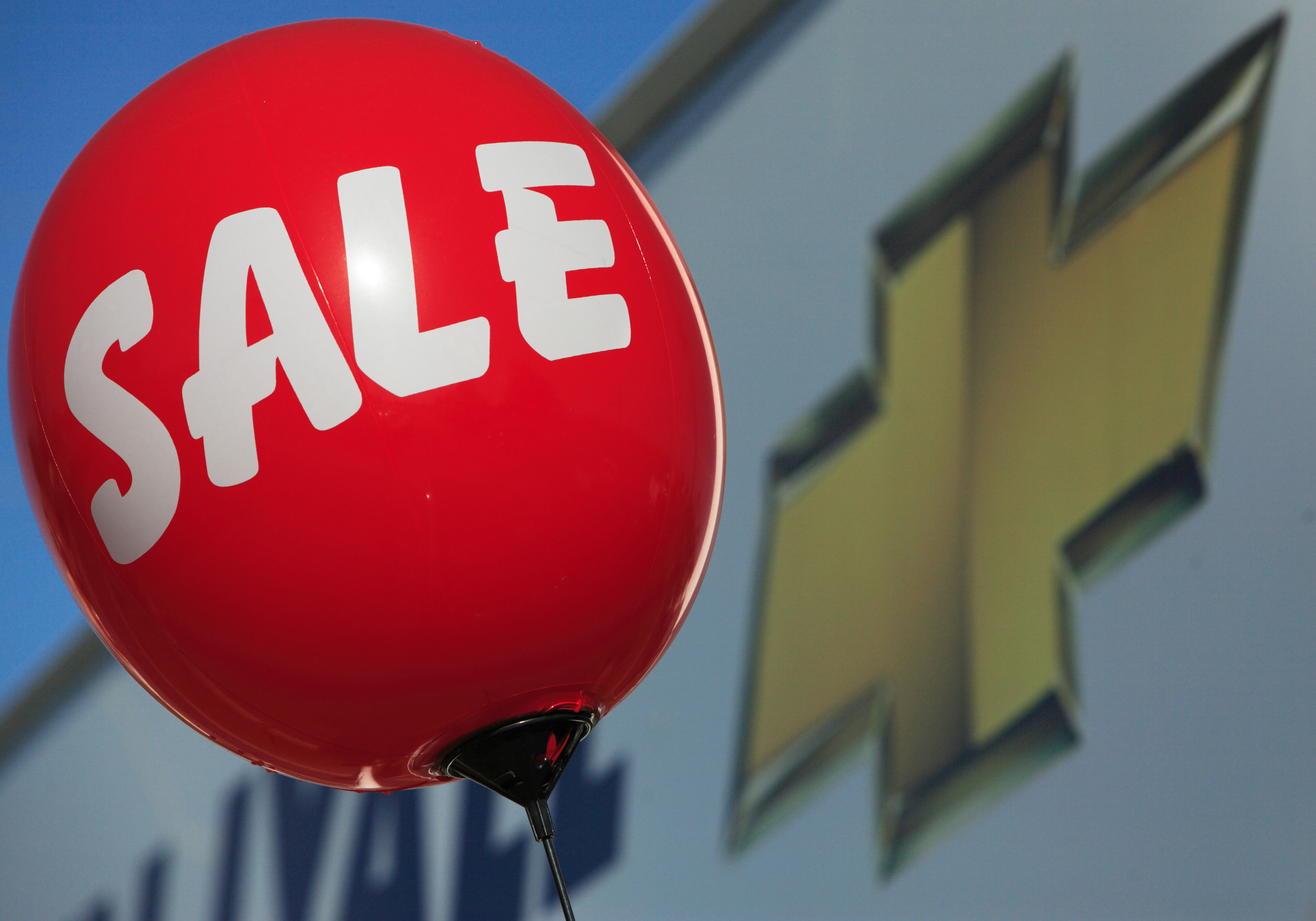 A balloon alerting consumers of a sale floats near a sign at
