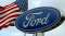 An American flag waves behind a Ford sign at a Ford dealership in San Bruno, California.