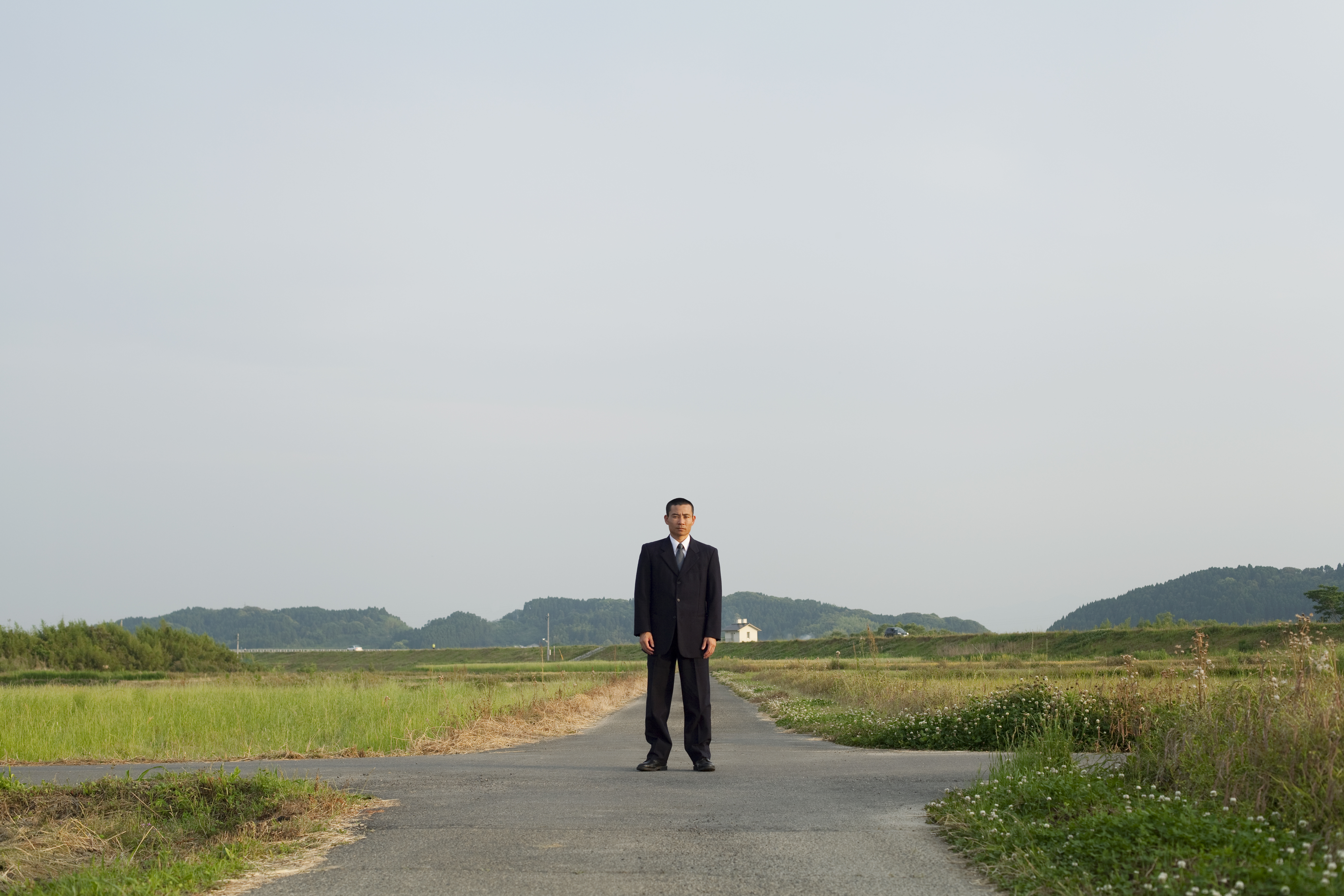 A businessman standing on the country road.