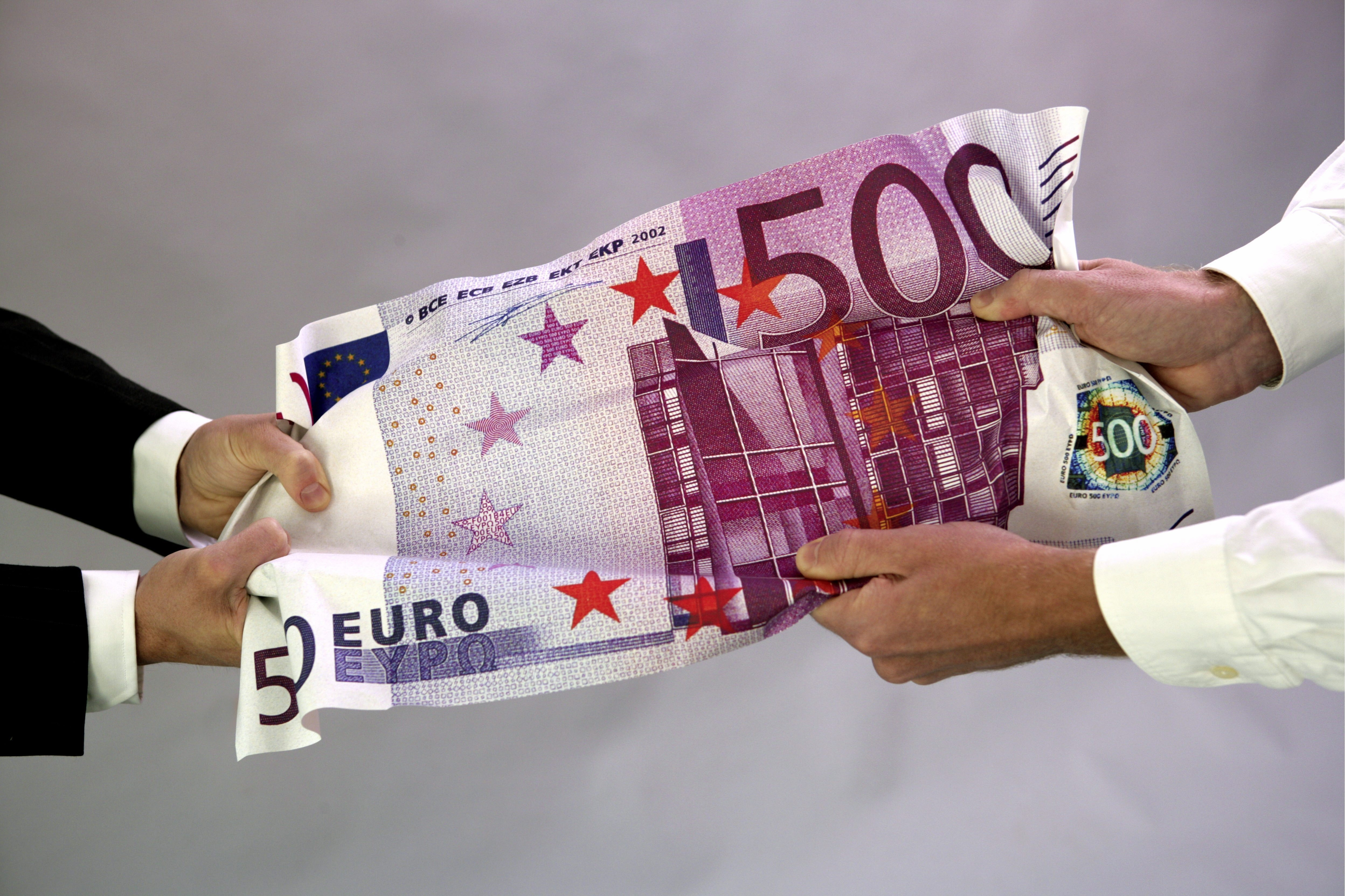 Hands pulling on 500 Euro banknote.