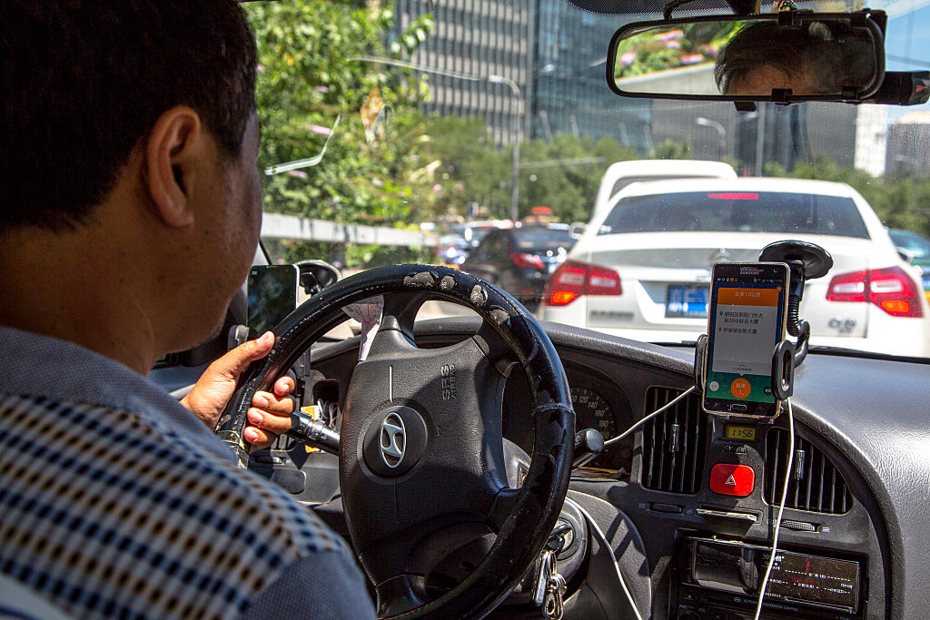 BEIJING, CHINA - 2015/08/04: A taxi driver is using Didi Dacha App while driving on the way.  China Investment Corporation (CIC) has made an undisclosed investment in Chinese taxi-hailing app maker Didi Kuaidi. (Photo by Zhang Peng/LightRocket via Getty Images)
