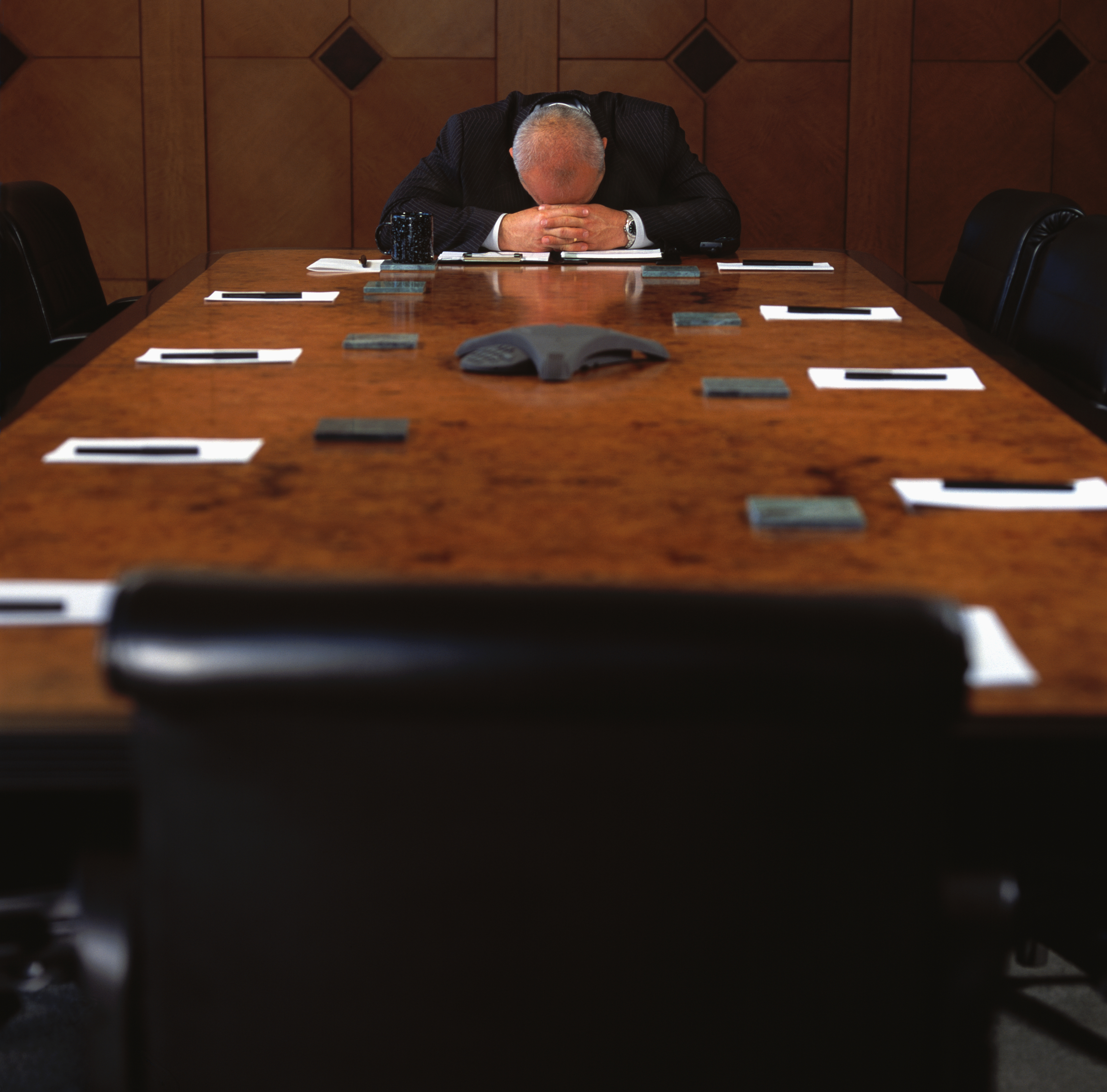 Man Sitting at Empty Conference Table with His Head Down