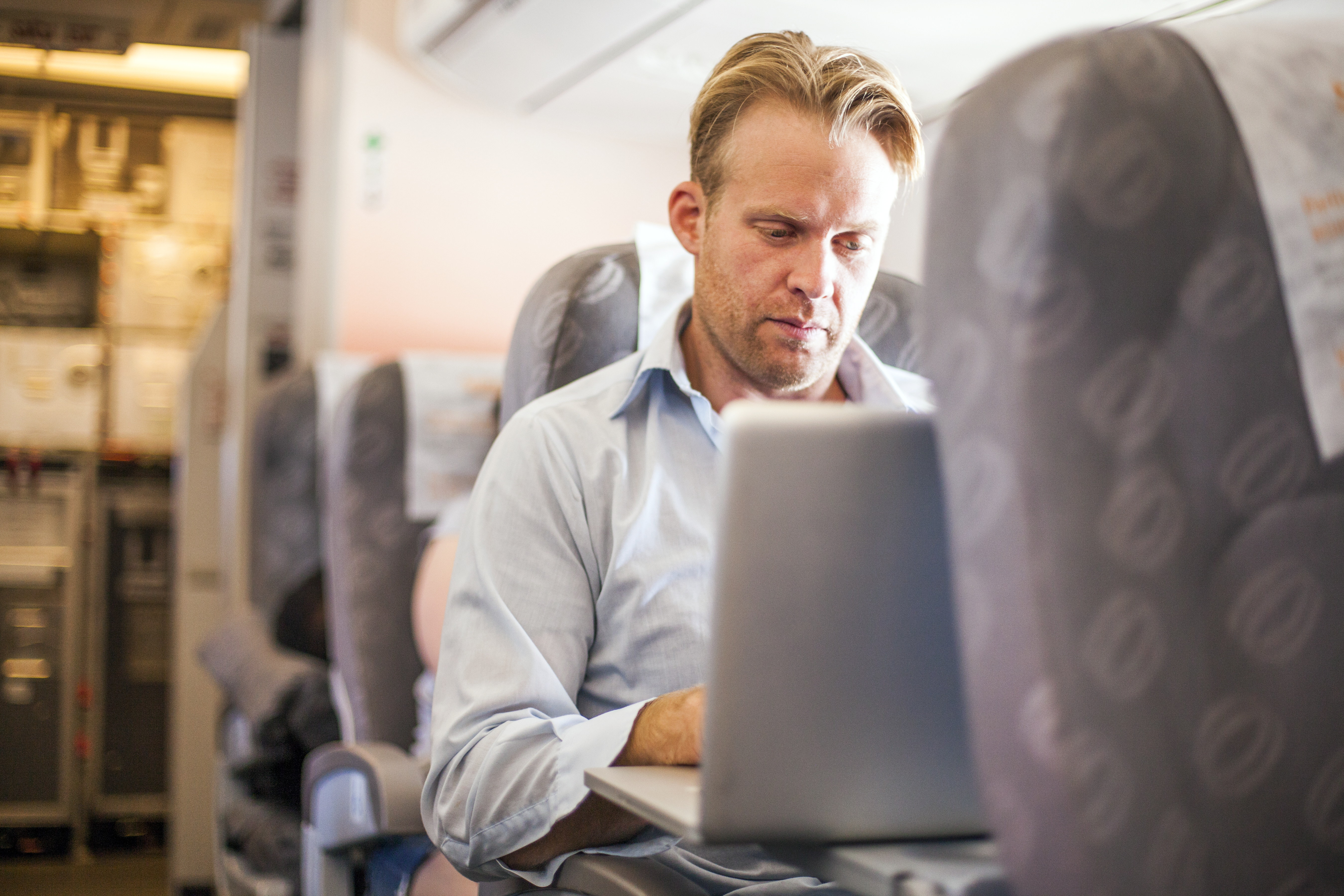 A businessman working on a lap top computer in an airplane.