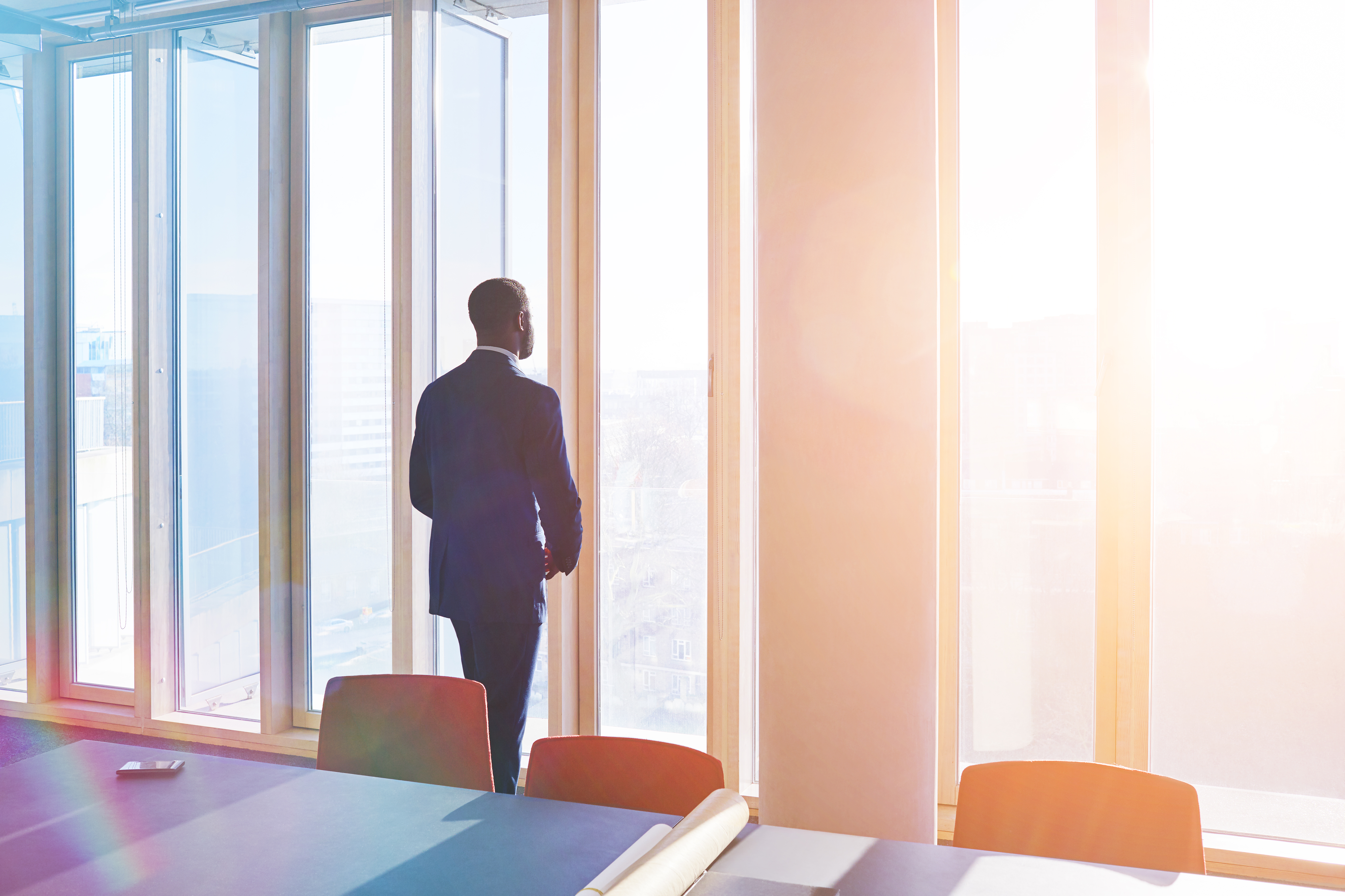 Businessman looks out of office window over city