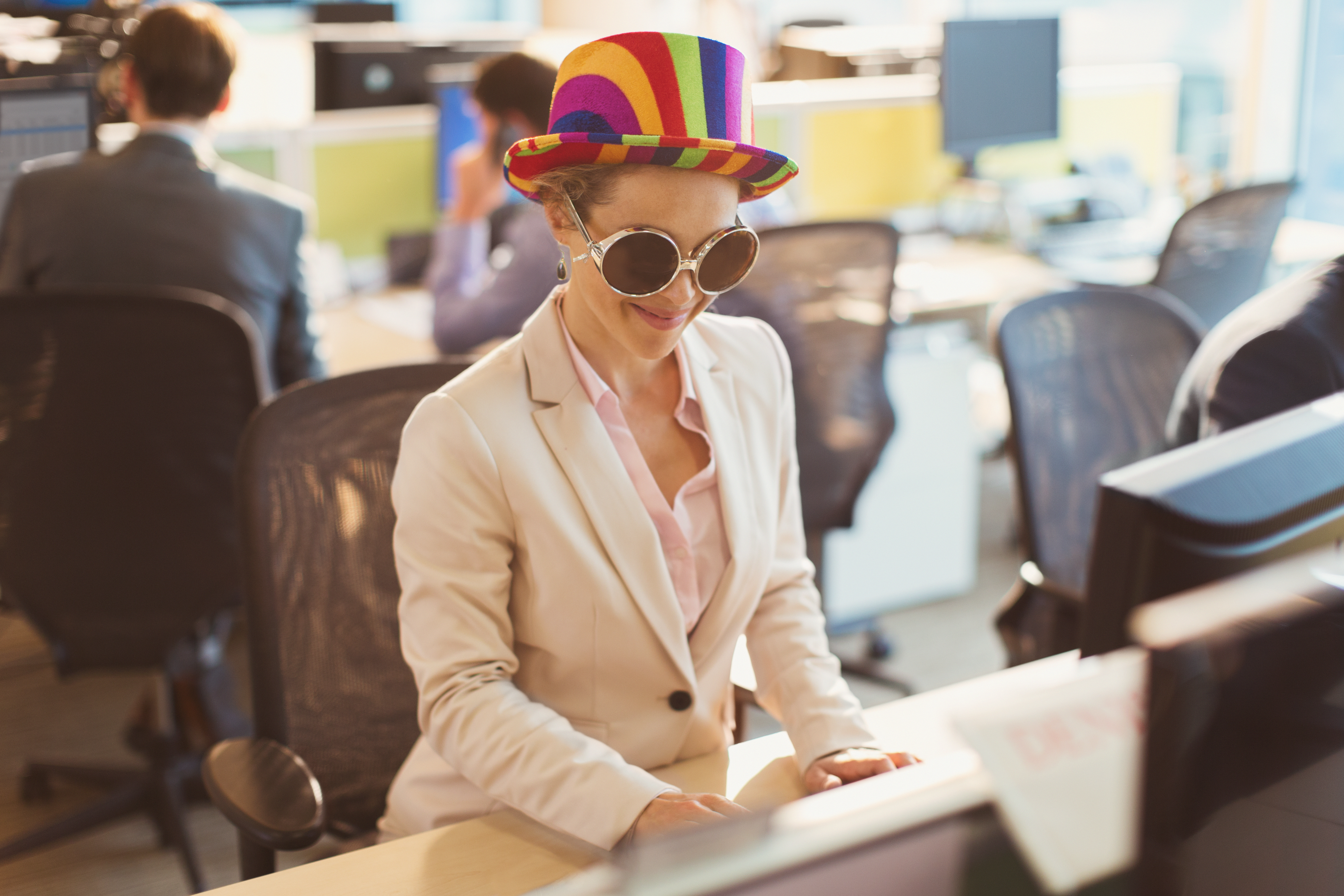 Playful businesswoman wearing silly sunglasses and striped hat at computer in office