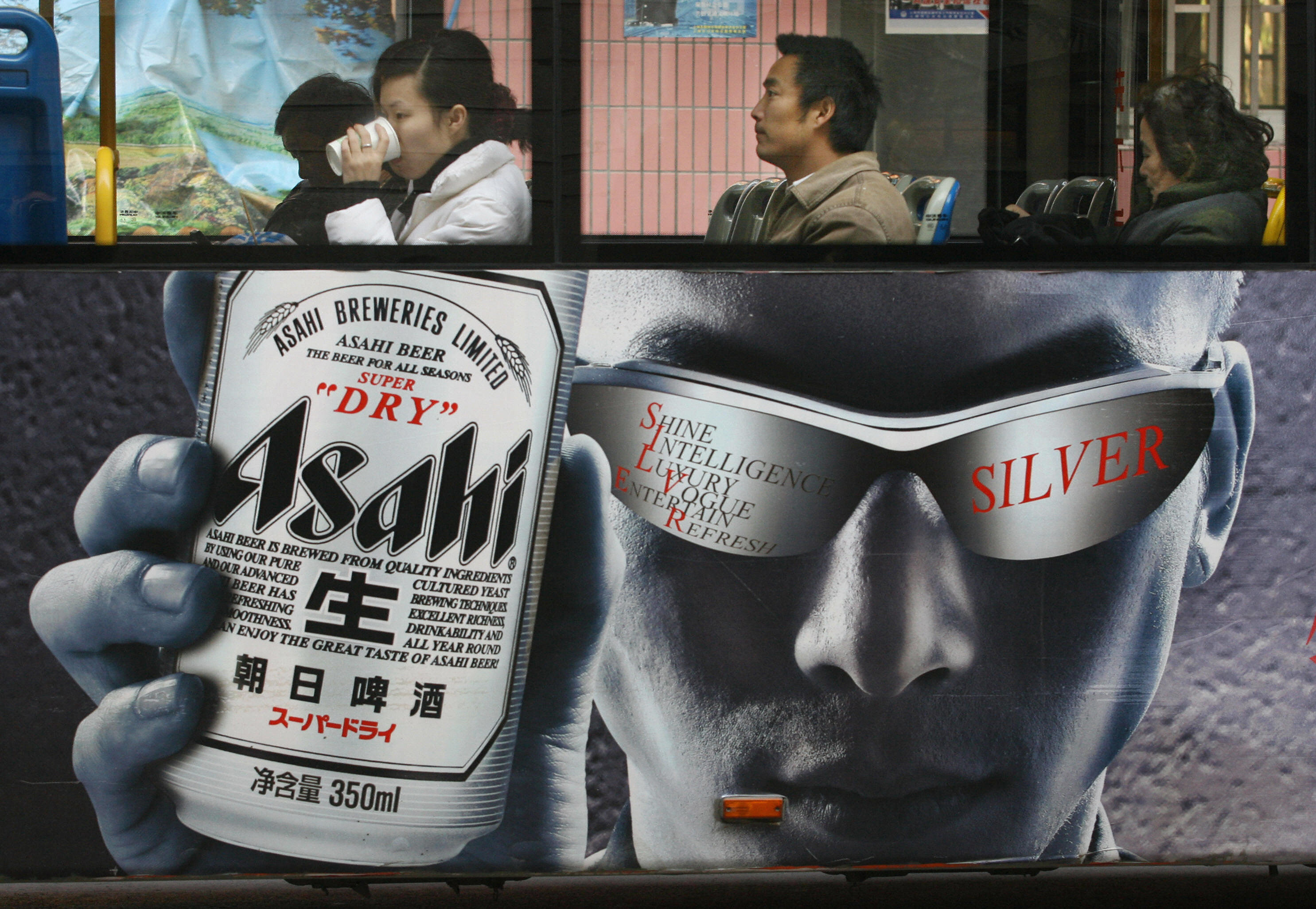 Bus passengers sit above an ad for Asahi