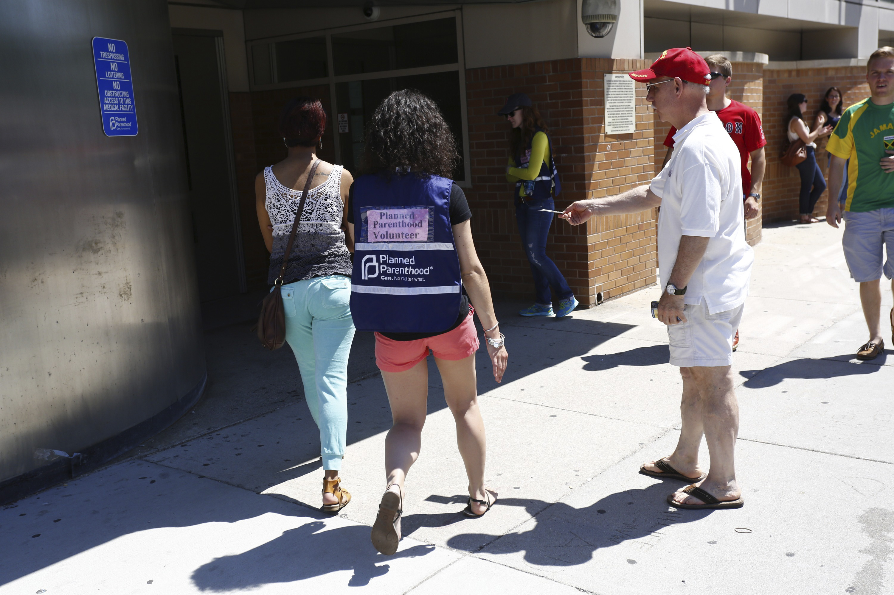 An abortion protester offers a pamphlet to a woman being escorted by a volunteer in front of a Planned Parenthood clinic in Boston, Massachusetts