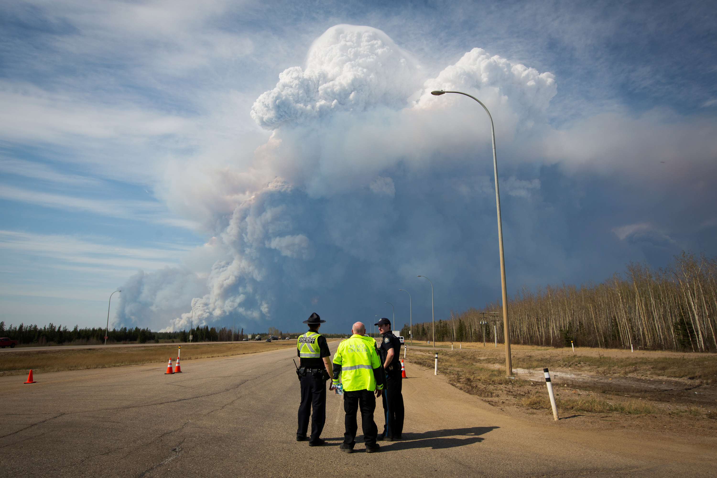Officers look on as smoke from Fort McMurray's raging wildfires billow into the air after their city was evacuated