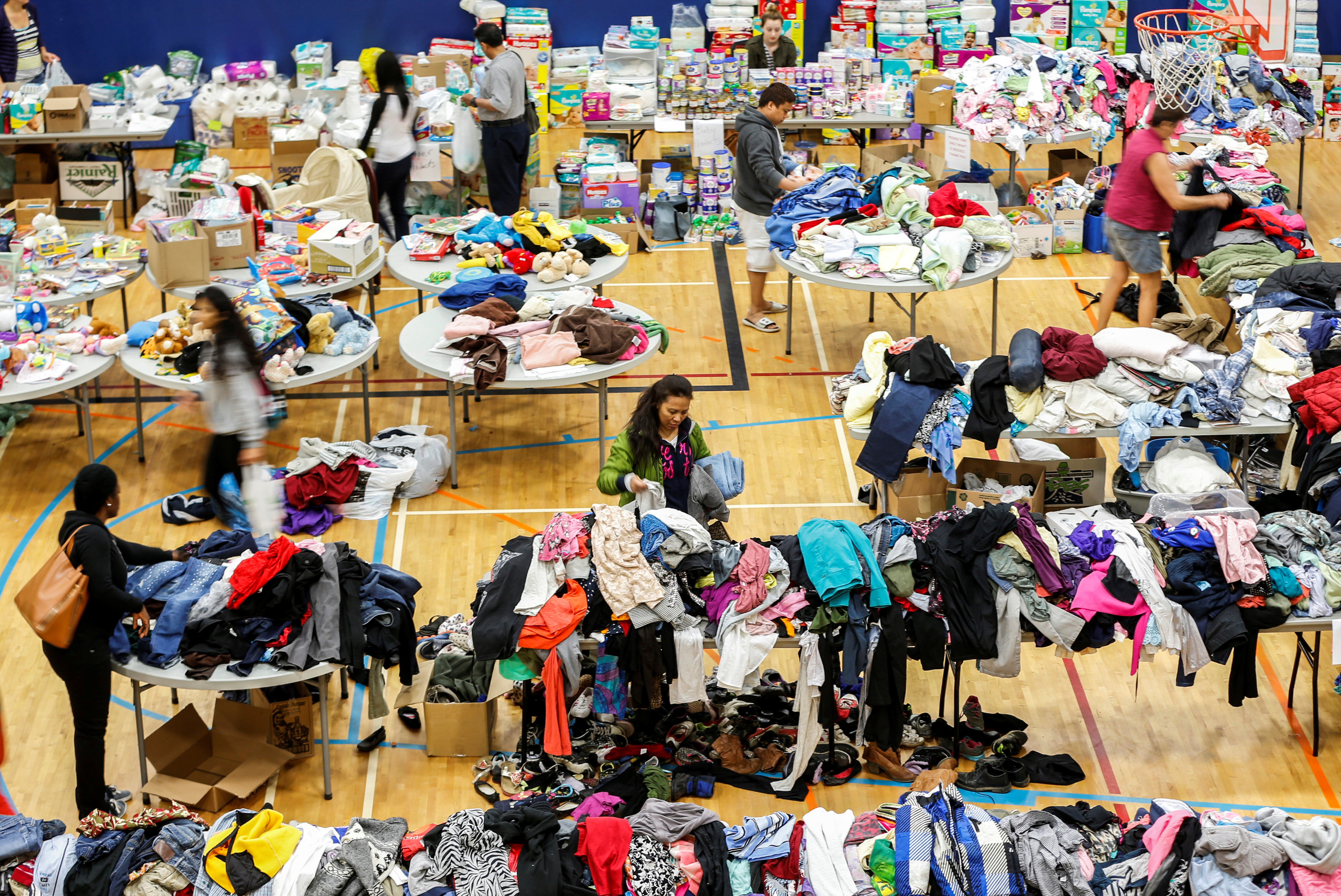 """Evacuees from the Fort McMurray wildfires look through donated goods and clothing at the """"Bold Center"""" in Lac la Biche"""