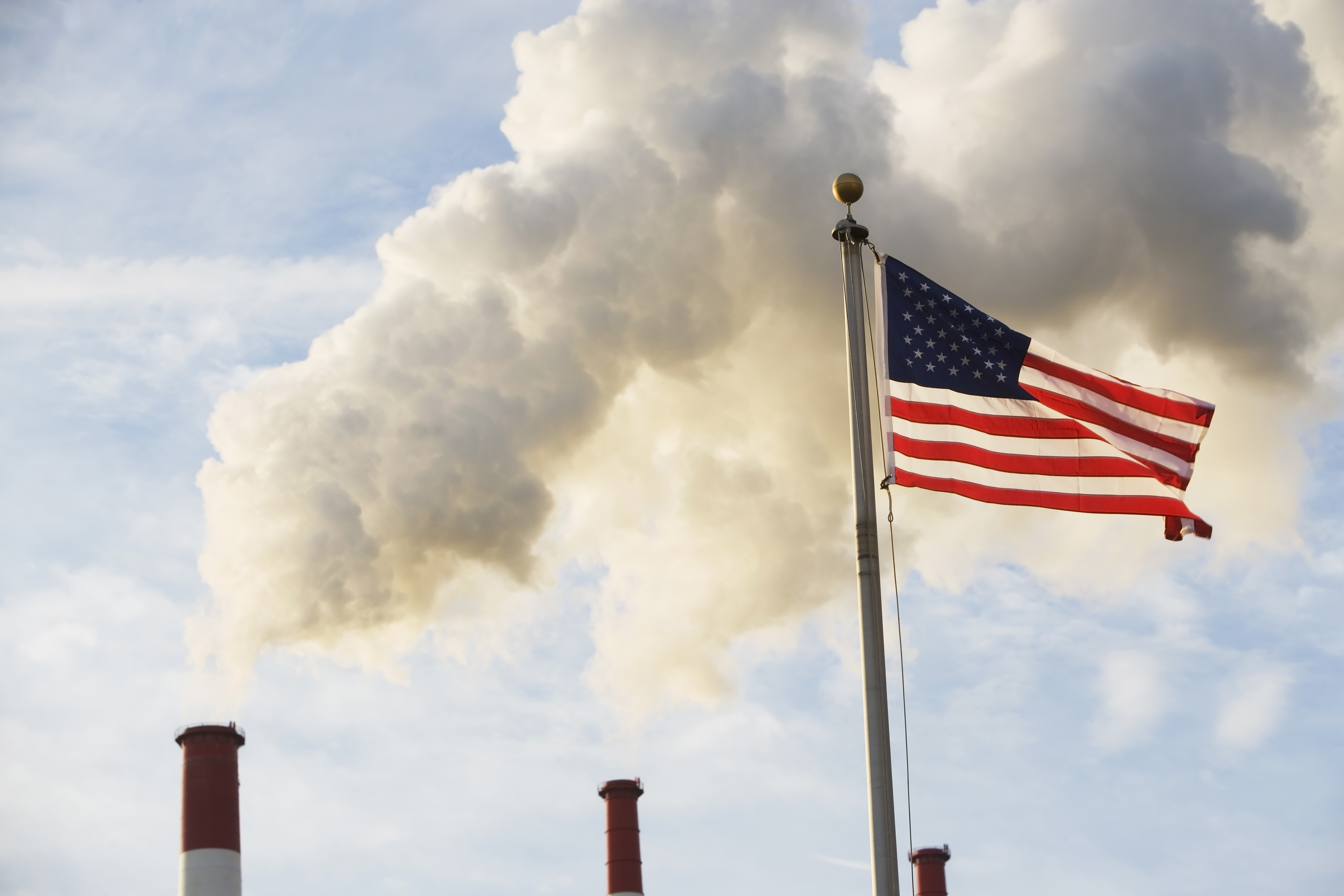 USA, New York State, New York City, American flag in front of smoke stacks