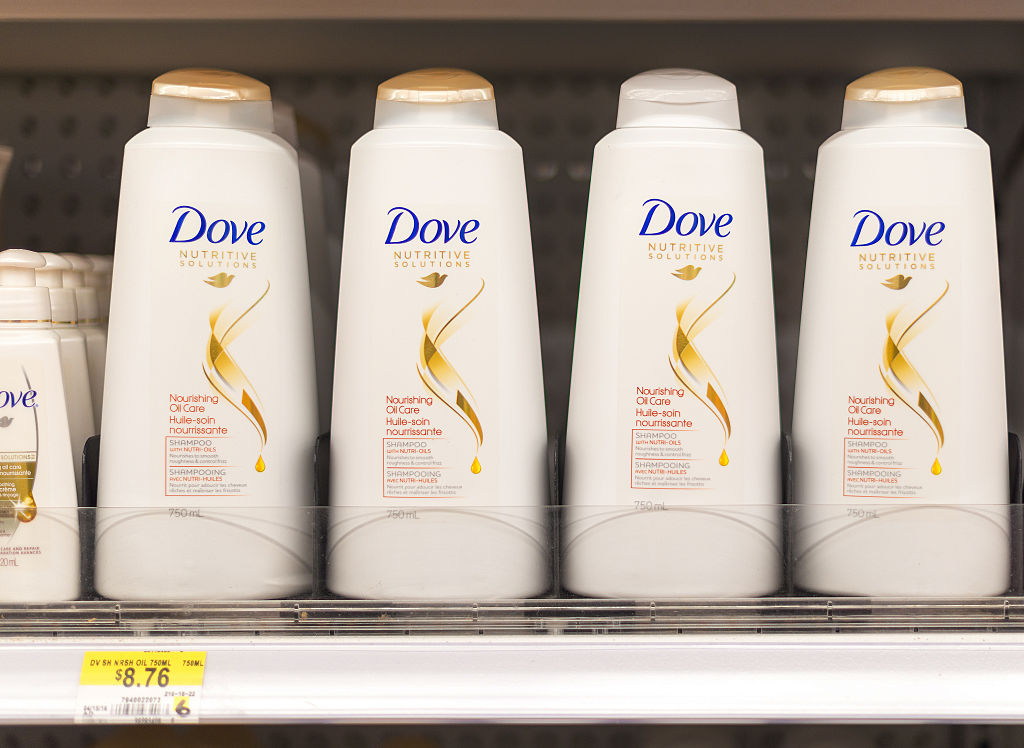 Dove shampoo and conditioner bottles in a shelf. Dove is one