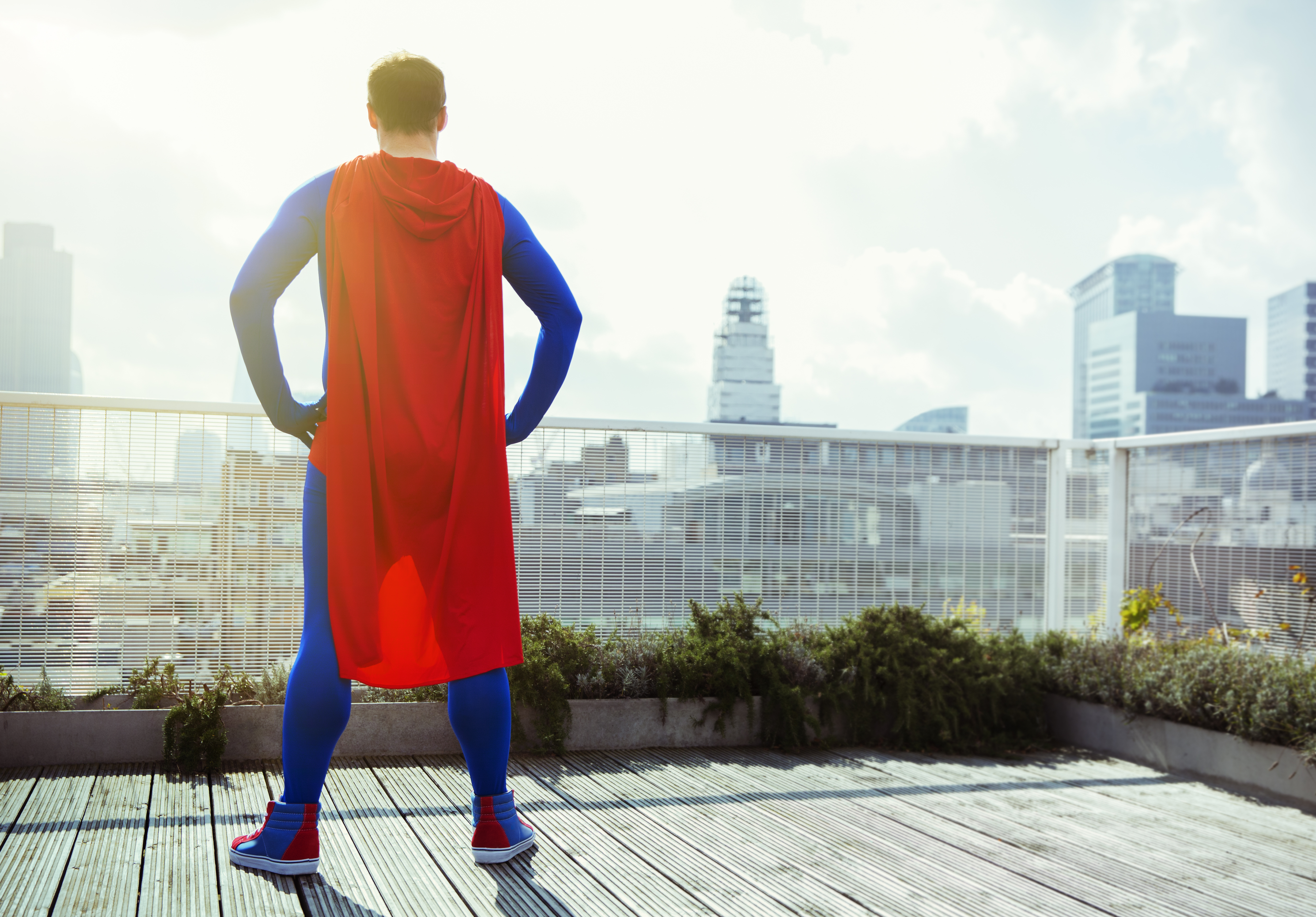 Superhero looking at view from city rooftop