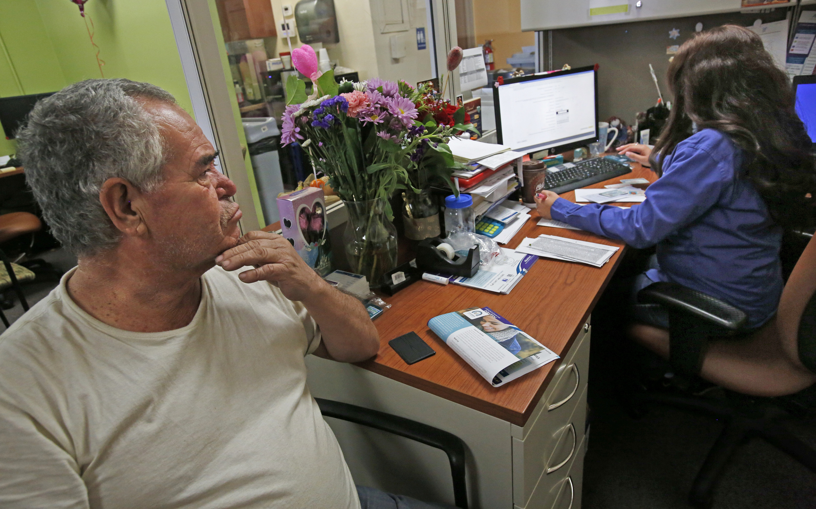 LOS ANGELES, CA. - FEBRUARY 14, 2015: Jose Mora, 62, signs up for Obamacare with Kristie Navarro, ri