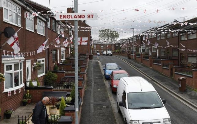 A man leaves his home on Wales Street in Oldham, northern England , June 13, 2016. Residents have temporarily renamed the road England Street during the European Soccer championships.