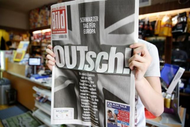 "A man holds up the German newspaper Bild with the titel ""OUTsch!"", for the camera, in Berlin"