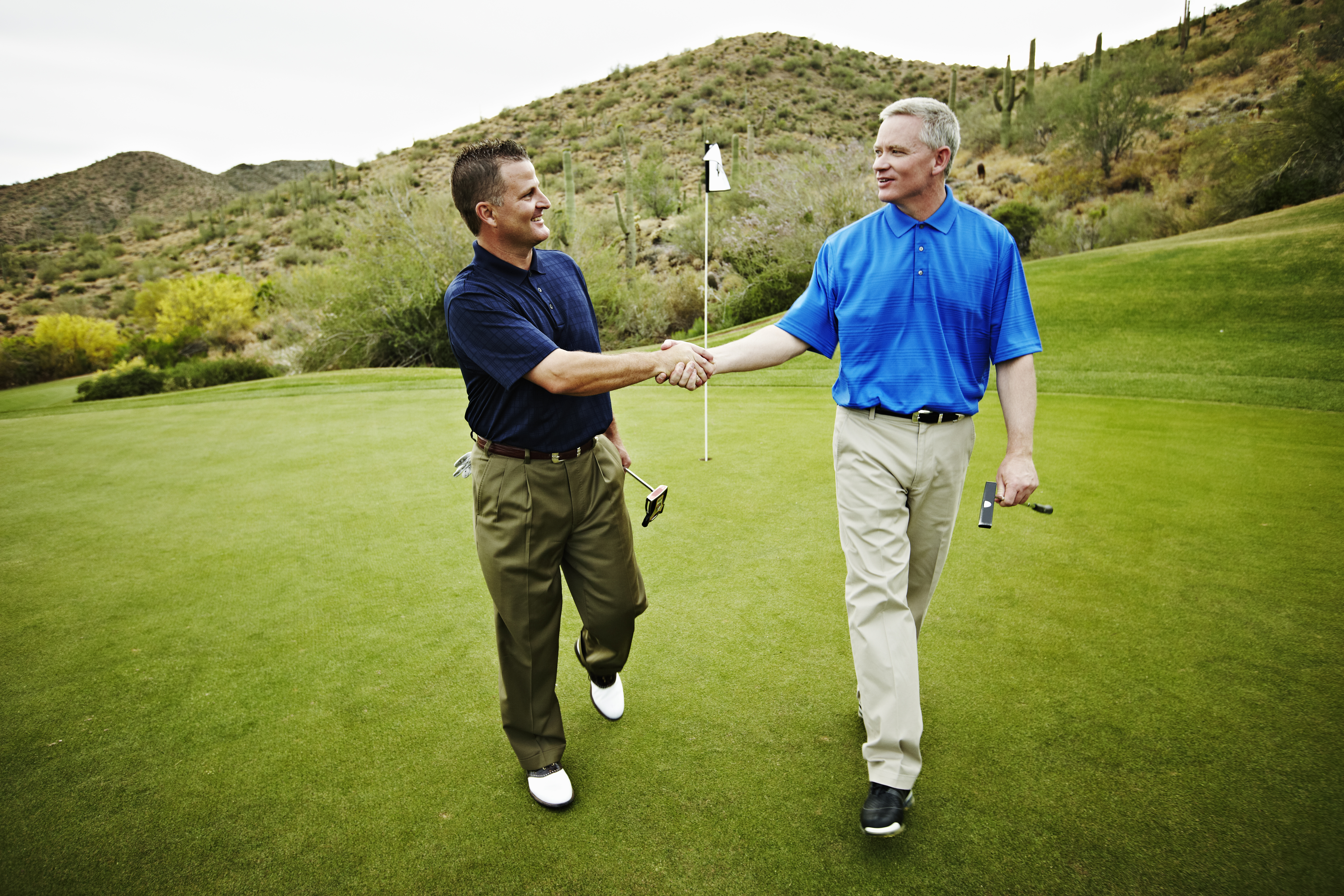 Two golfers walking off green shaking hands