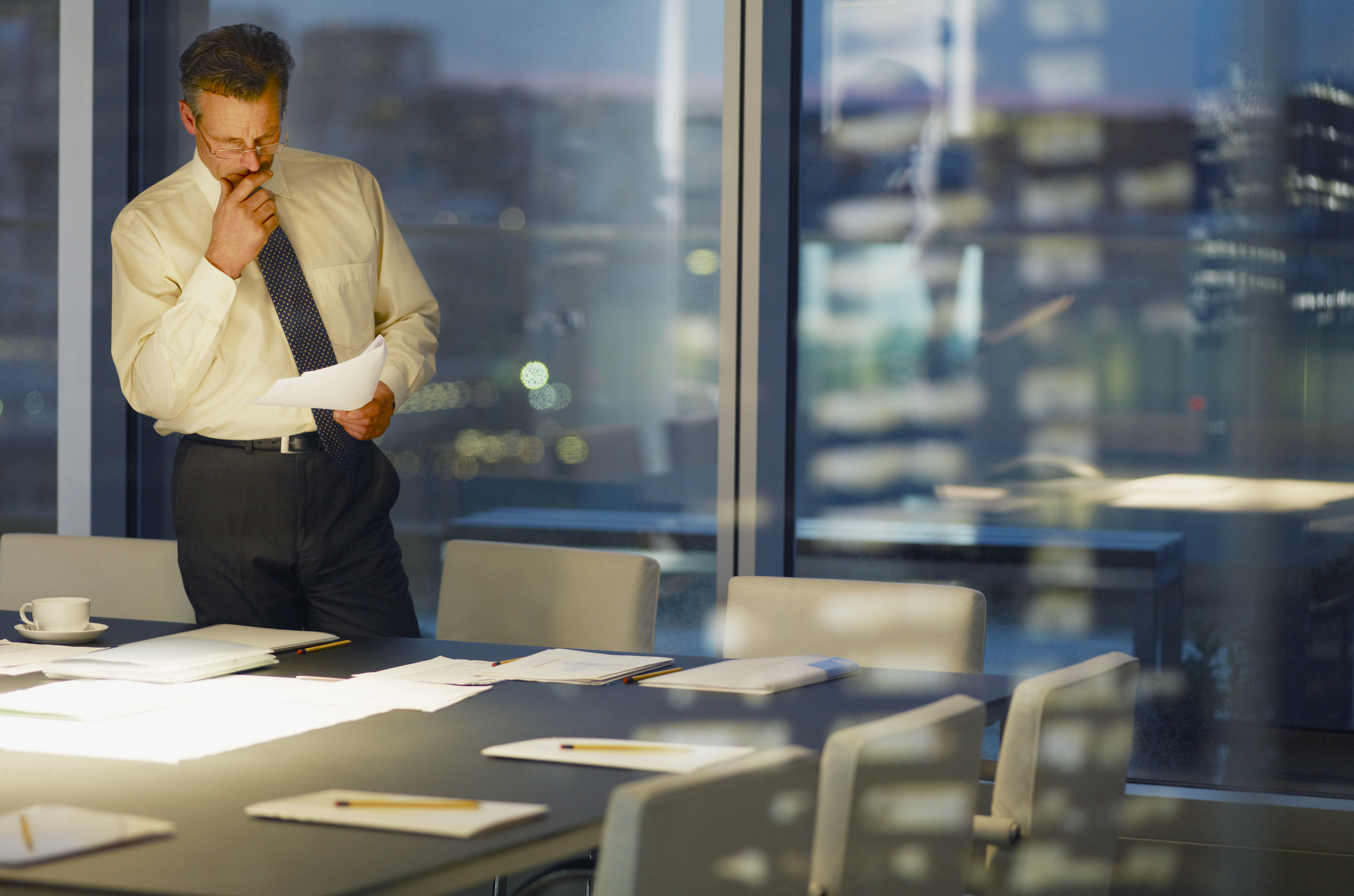Businessman standing at conference room table at night