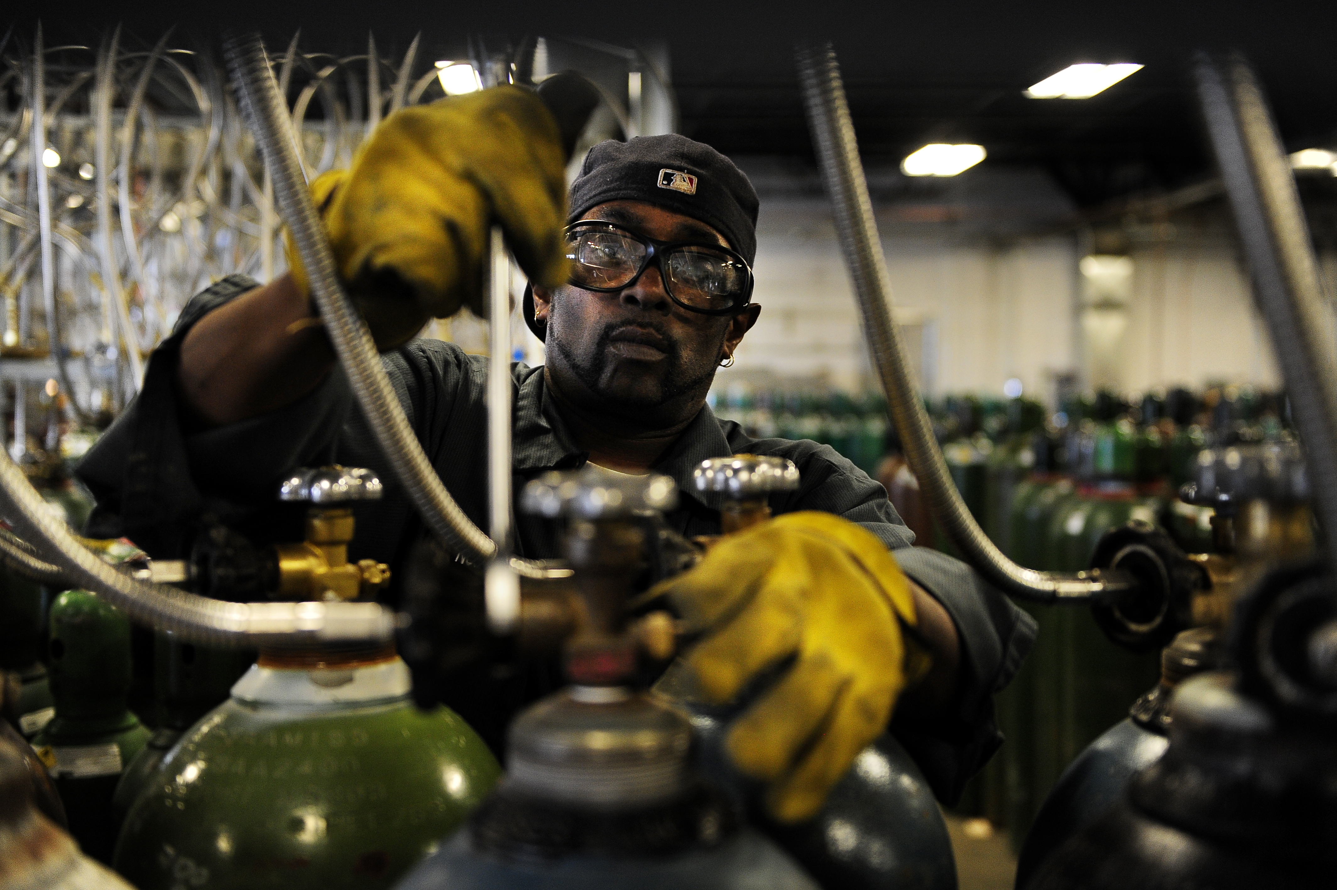 Cylinder filler Norman Coleman disconnects the lines from the nitrogen tanks he's just filled at the Airgas Intermountain Plant in Commerce City. Unemployment insurance tax rates are up about 40 percent this year compared to last in Colorado. But it all d