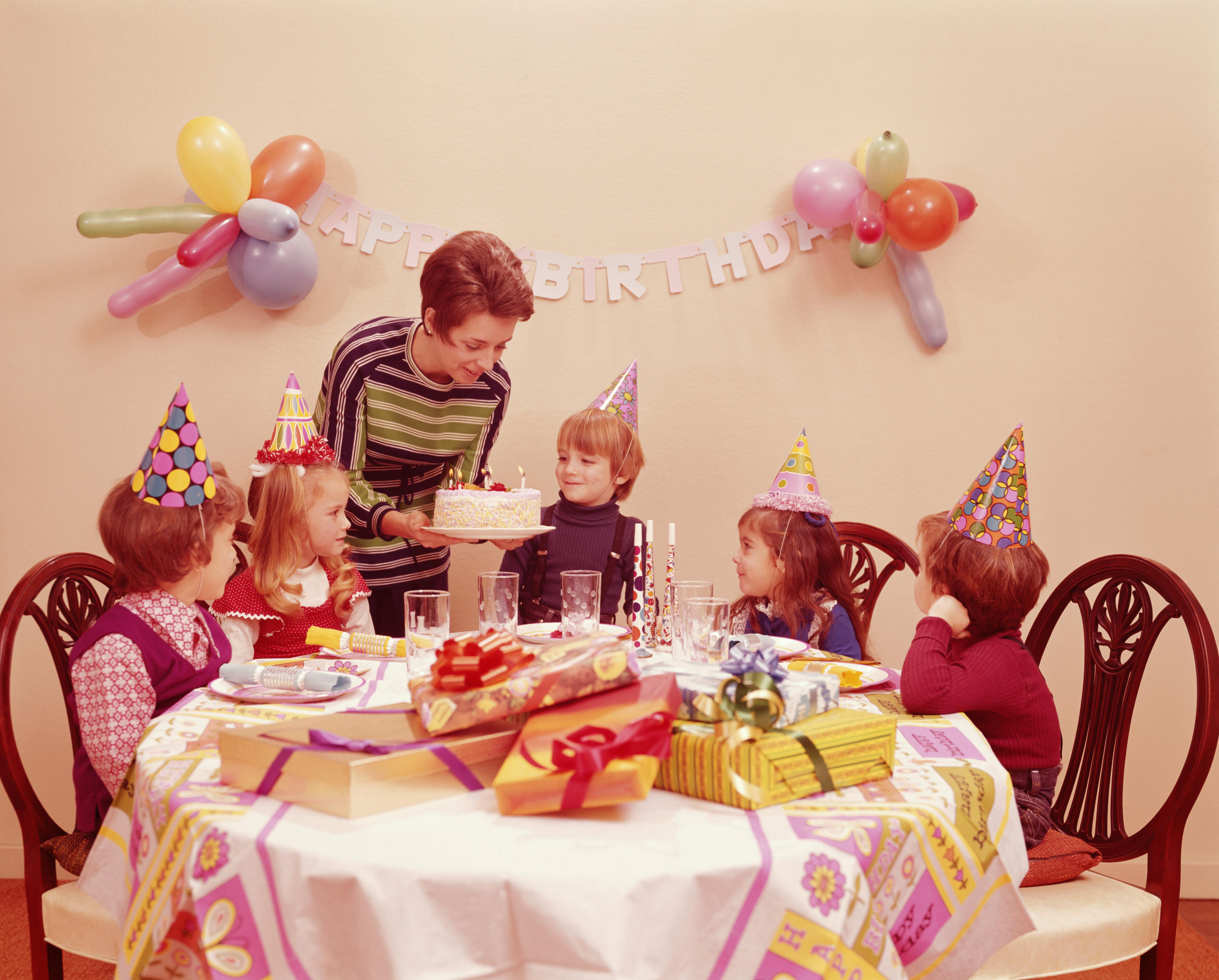 Mother serving birthday cake to children