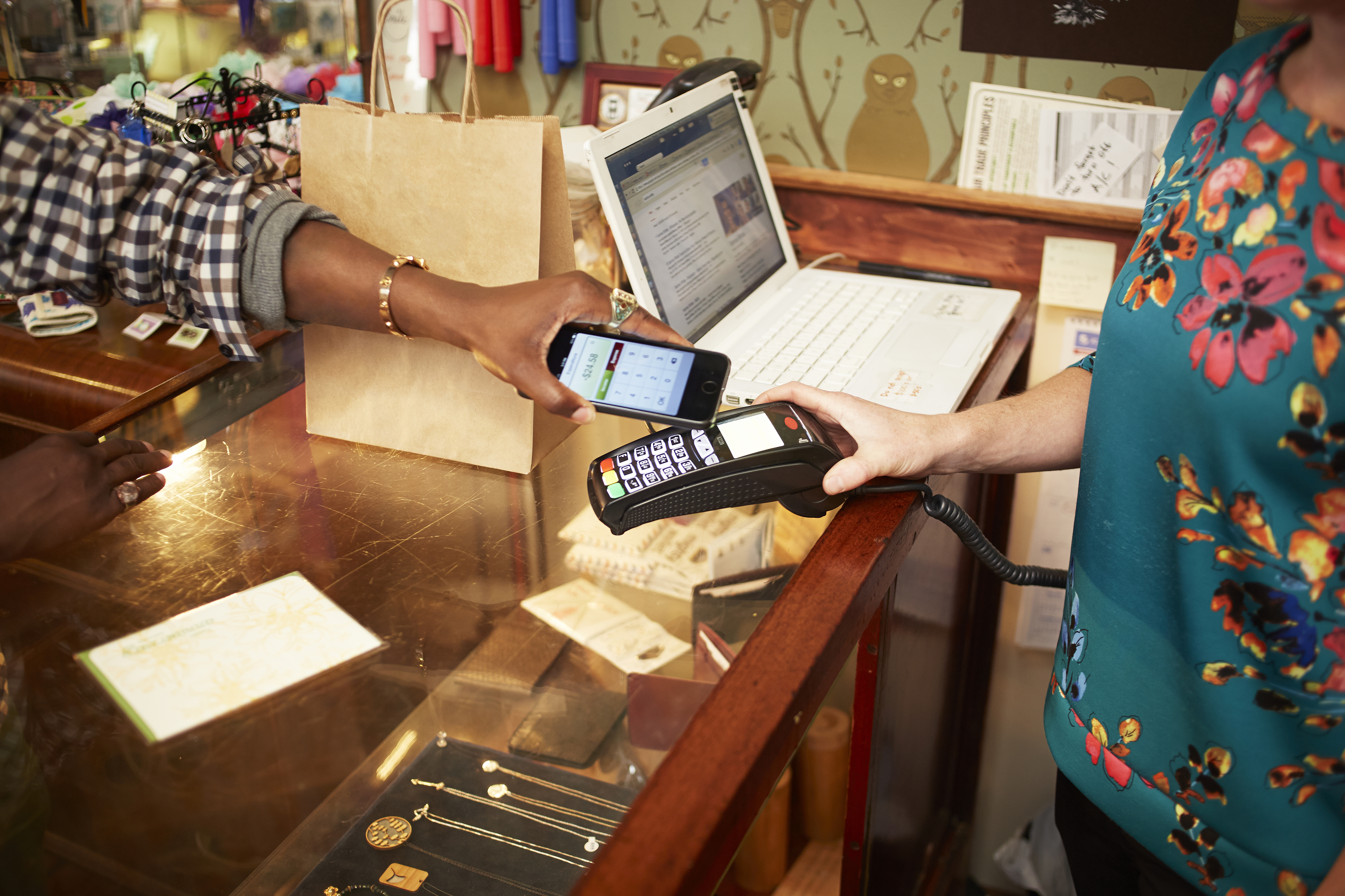Woman using cell phone for payment in store
