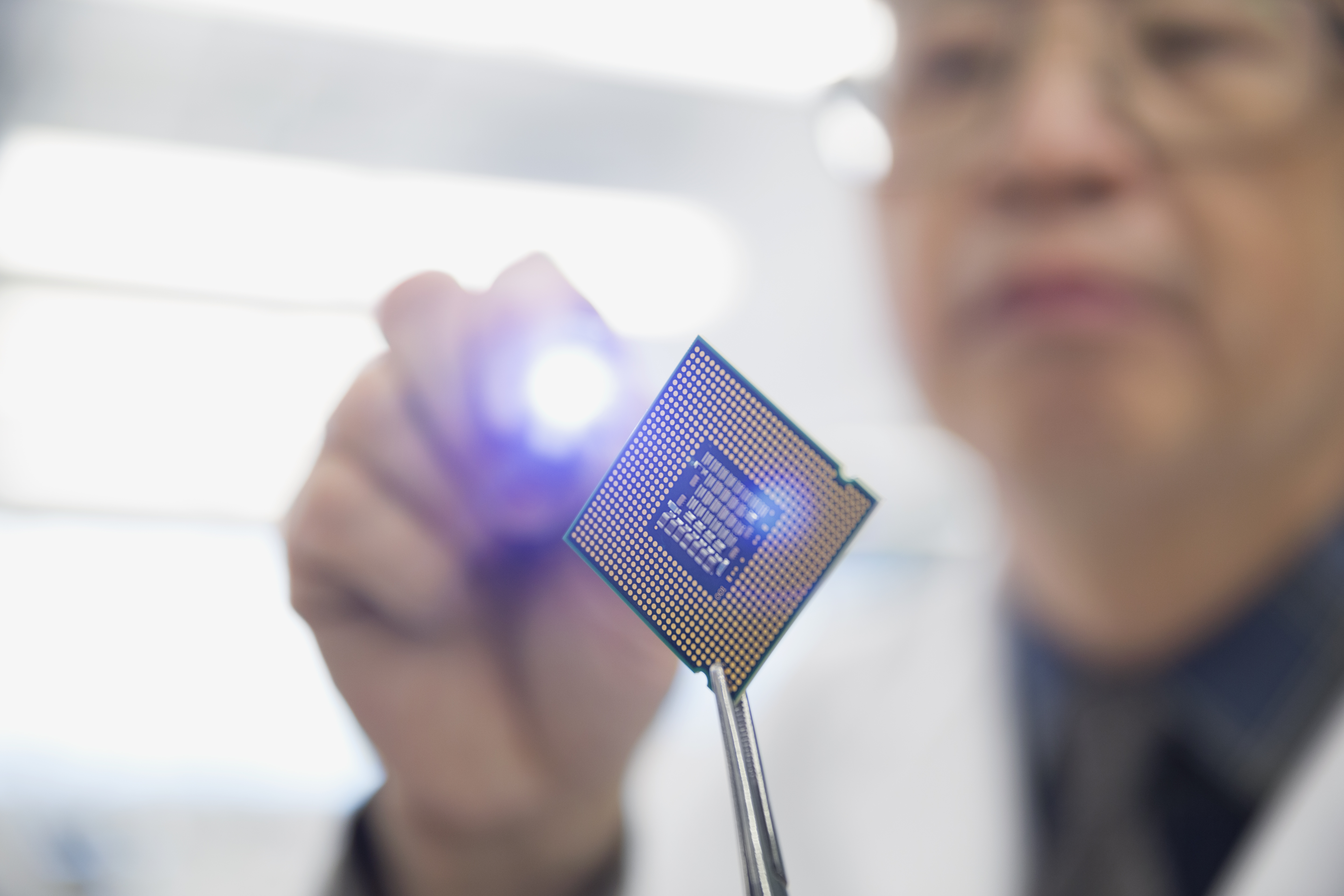 Focused engineer examining microchip with flashlight
