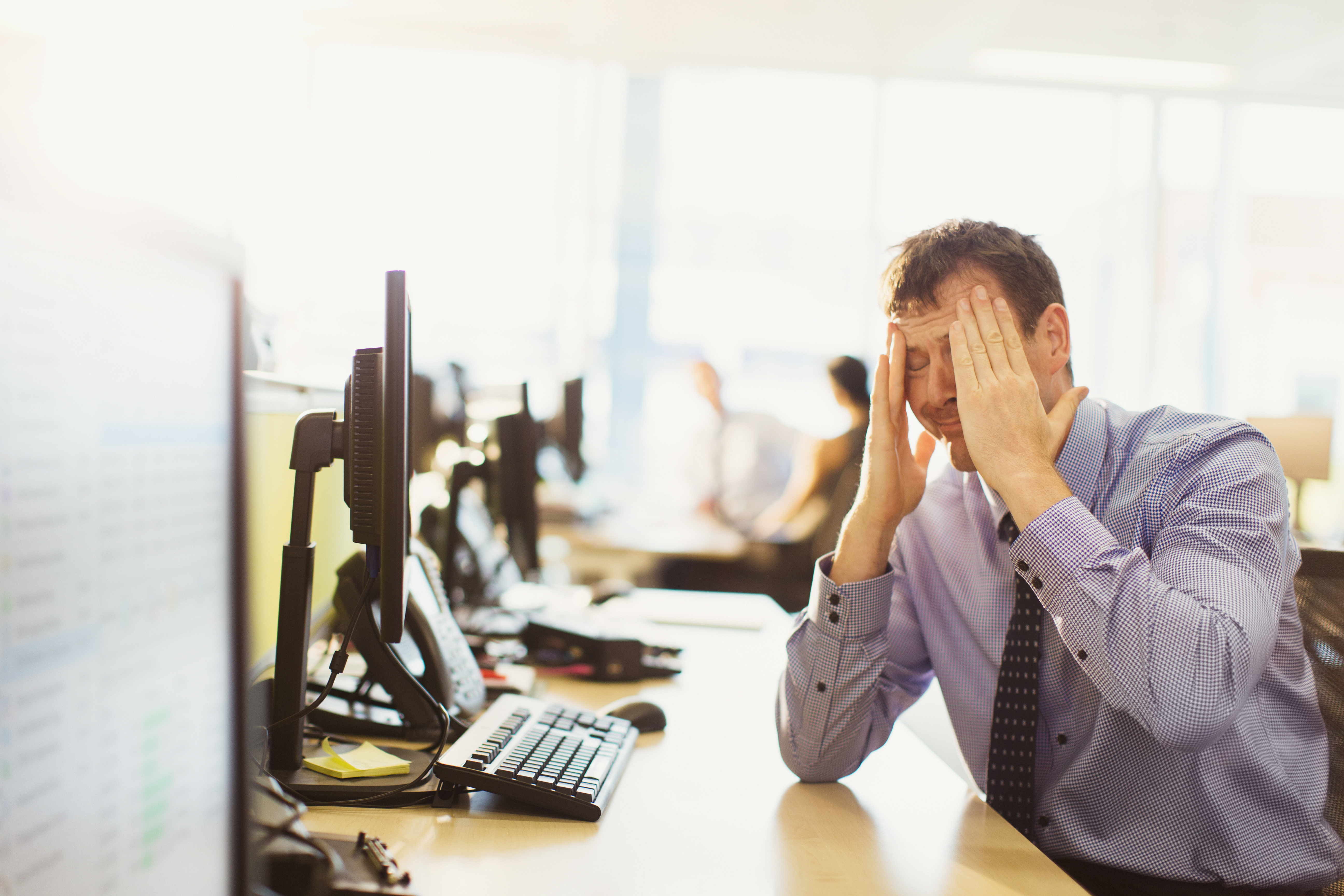 Stressed businessman with head in hands at office desk