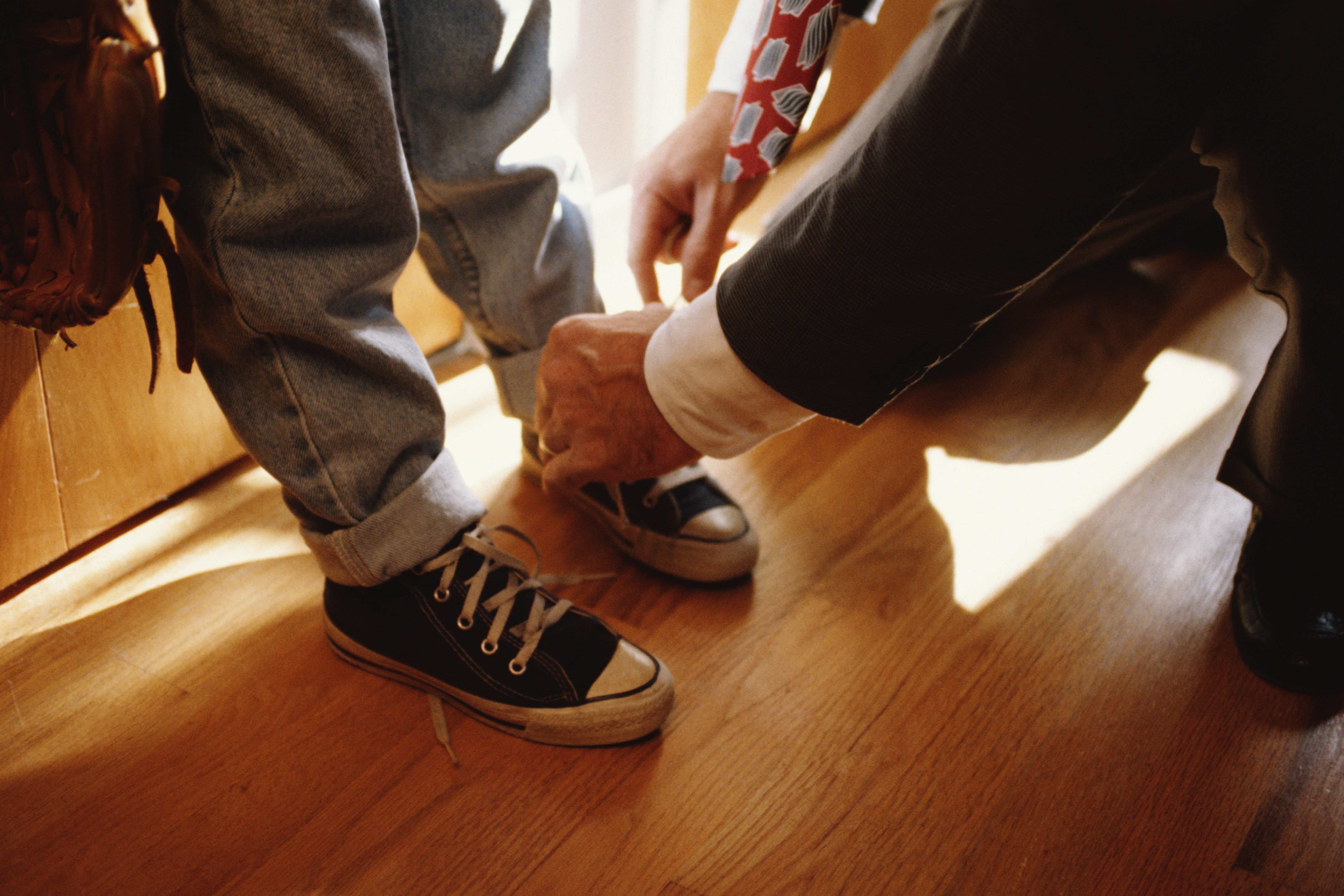 Father tying child's shoelaces