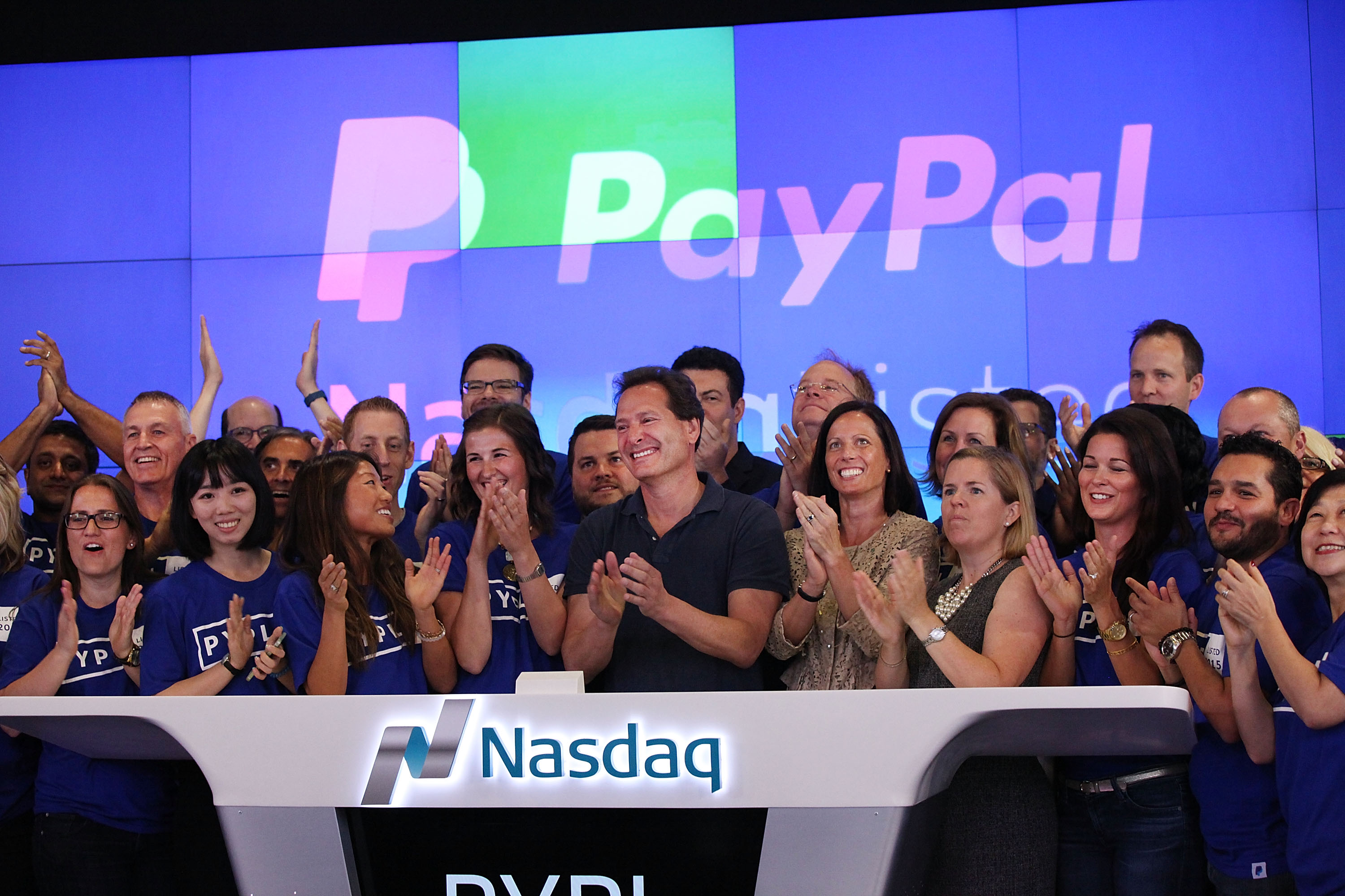 PayPal CEO Dan Schulman (center, with hands clasped) with co-workers on July 20, 2015, the day PayPal's stock began trading on the Nasdaq.