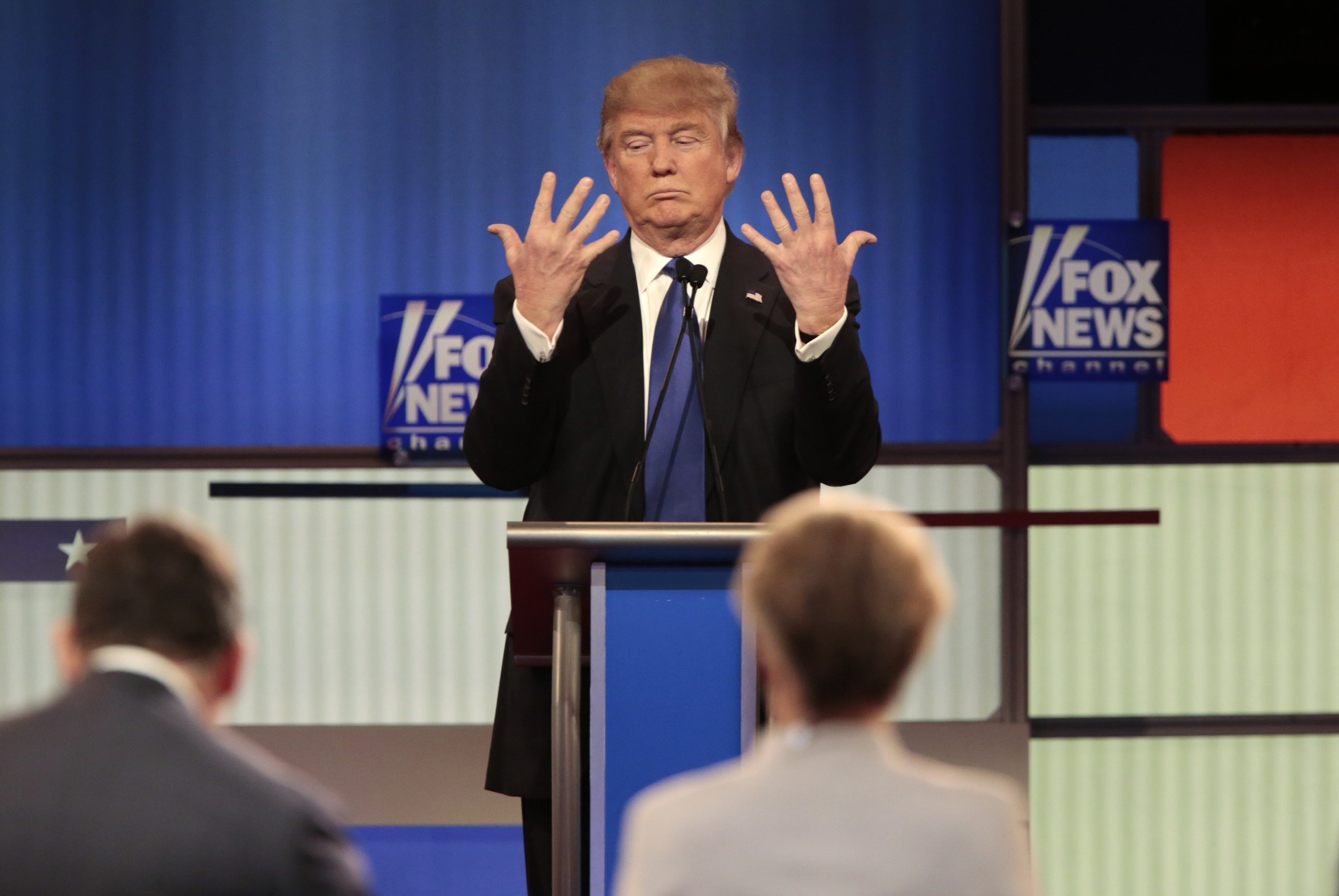 Republican U.S. presidential candidate Trump shows off the size of his hands as Fox News Channel moderators Baier and Kelly look on at the U.S. Republican presidential candidates debate in Detroit
