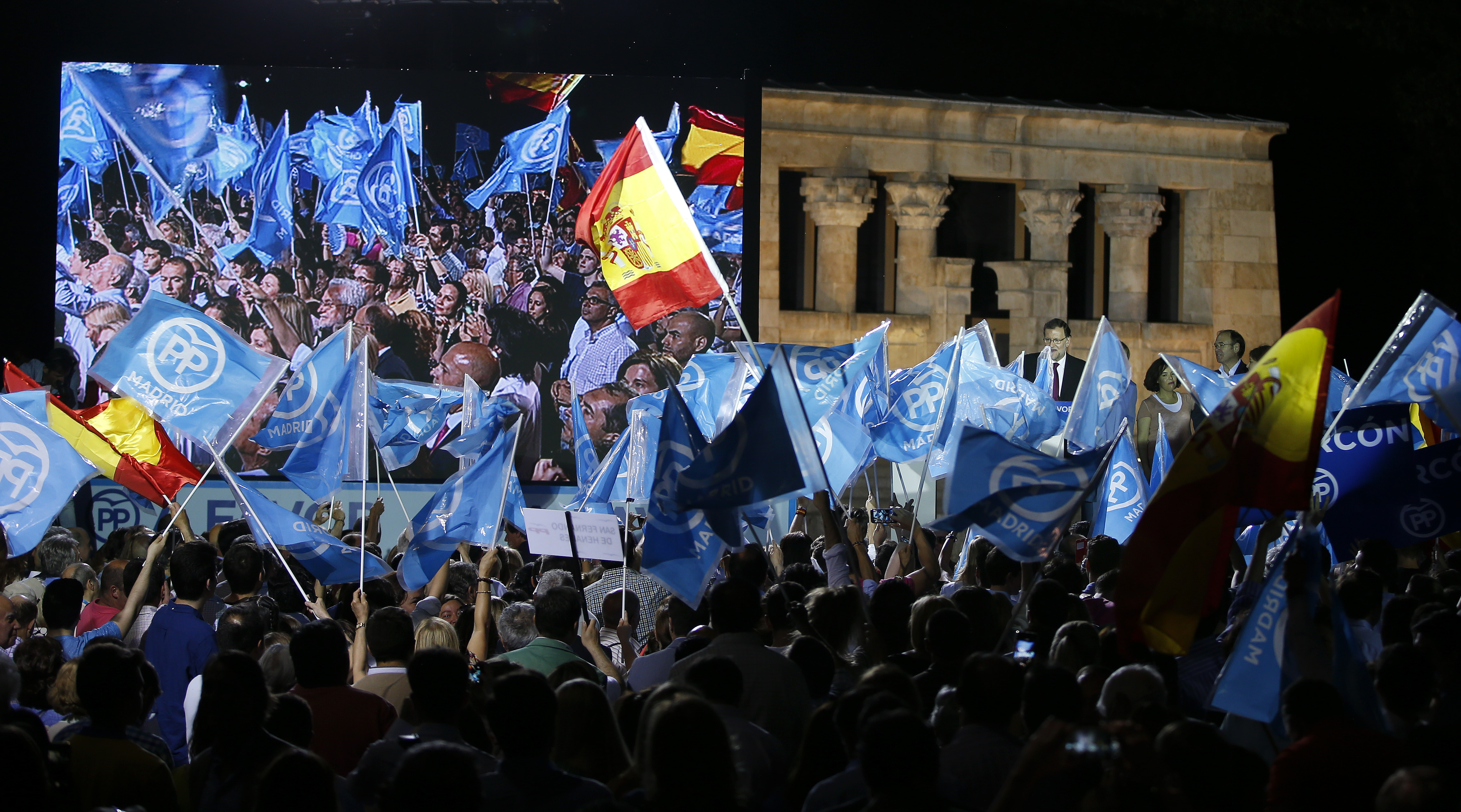 Supporters wave flags as People's Party (PP) leader Mariano Rajoy delivers a speech during a rally at the start of the official campaign period for Spain's general election in Madrid