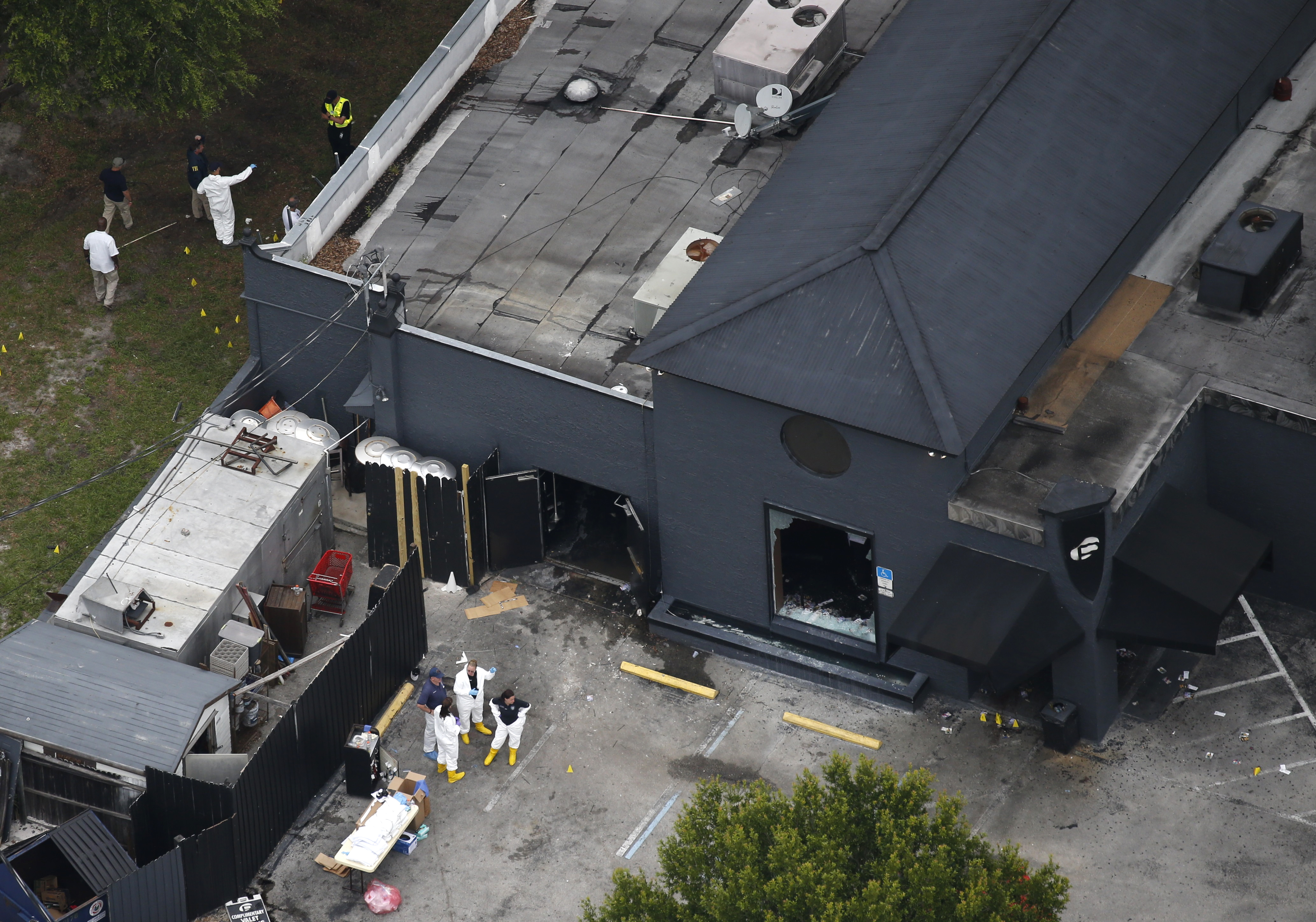 Police forensics investigators work at the crime scene of a mass shooting at the Pulse gay night club in Orlando