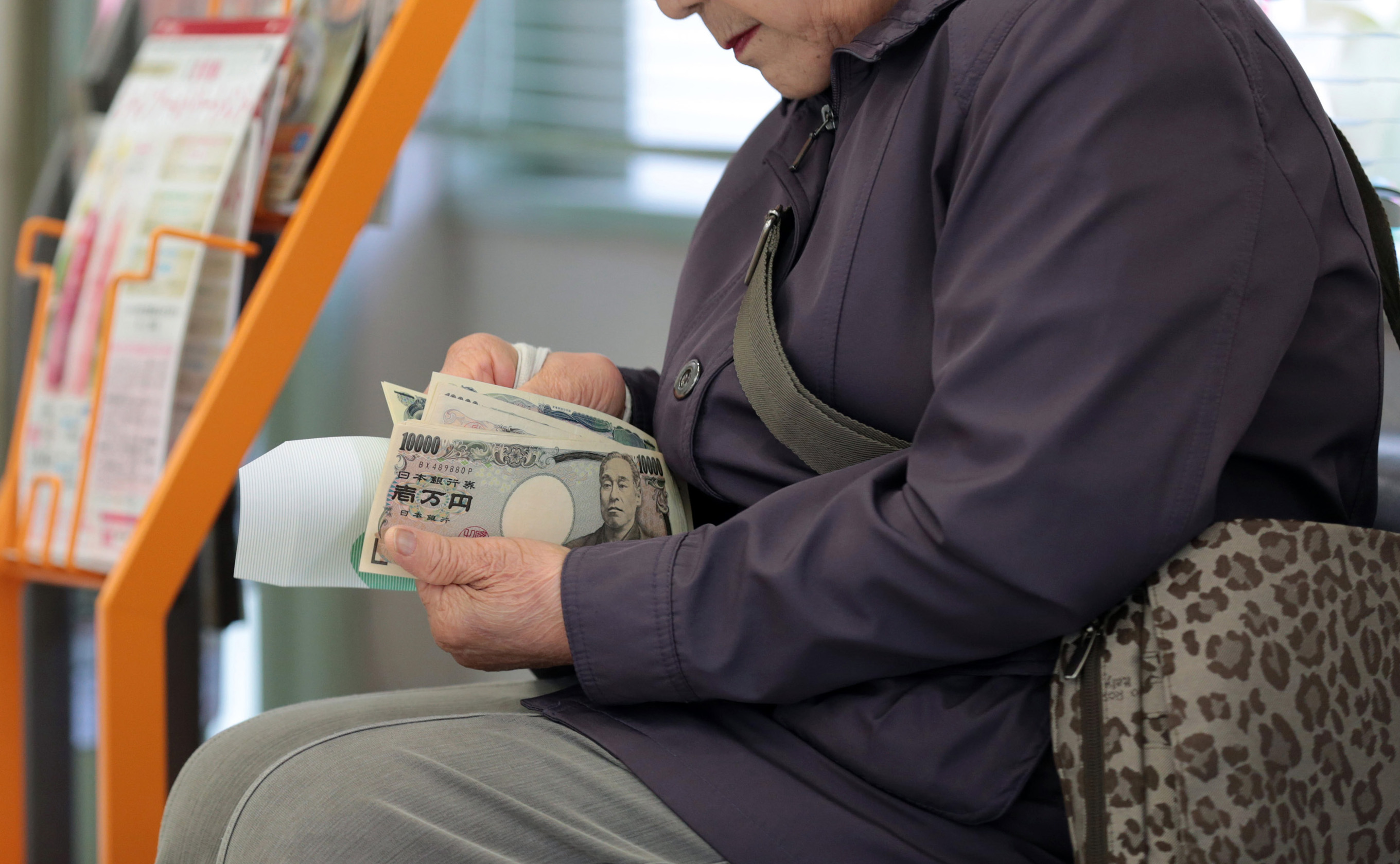 A customer counts her money after making a withdrawal at a