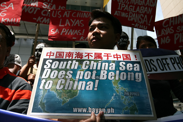 Protesters holding posters against China's incursions in the