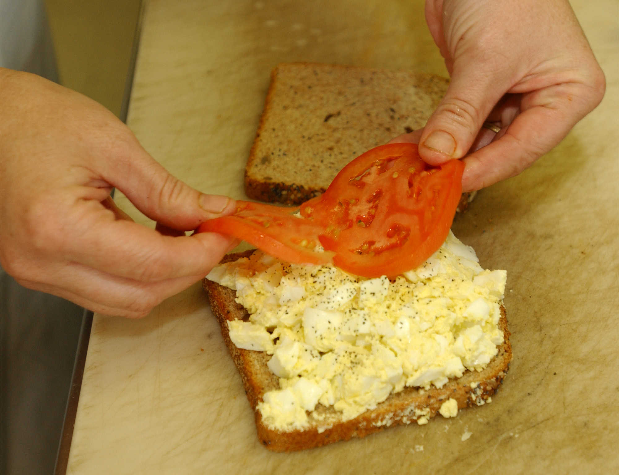 Simone Ryle, owner of Dantes in One city Center lays a couple of tomato slices on an egg salad sandw