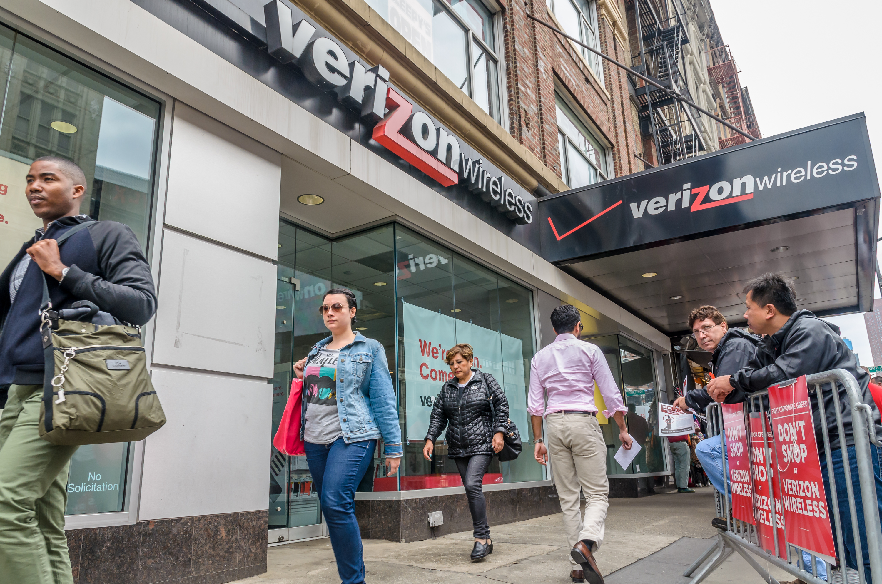 Striking workers on a picket line outside a Verizon retail