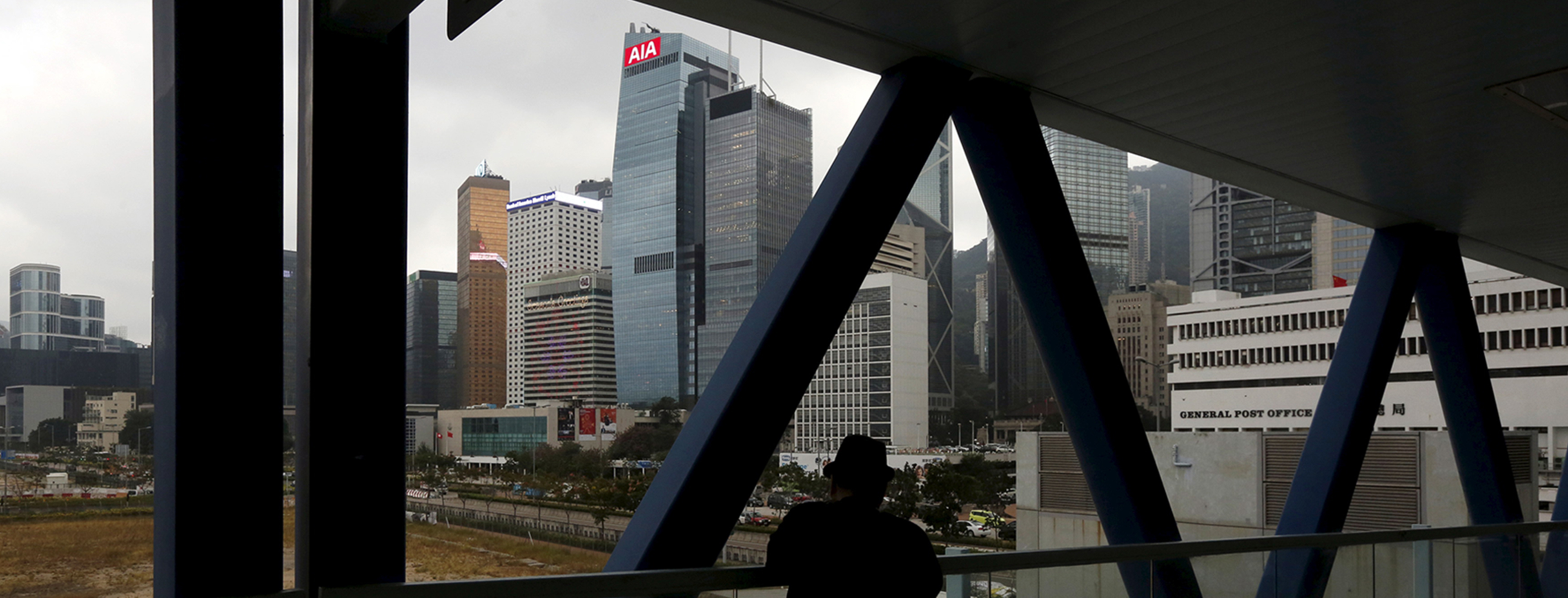 A man stands on a footbridge in front of AIA Central at the financial Central district in Hong Kong, China