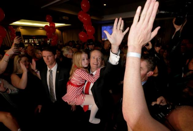 Australian Labor Party opposition leader Bill Shorten high-fives with supporters as he holds his daughter Clementine at his election night party in Melbourne
