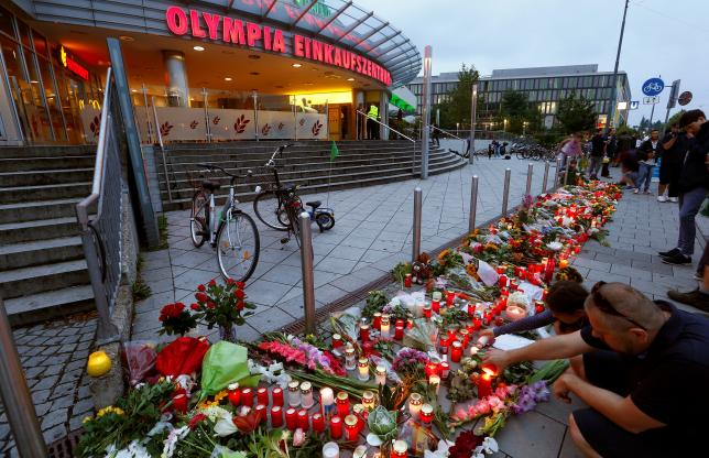 People light candles beside flowers laid in front of the Olympia shopping mall, where yesterday's shooting rampage started, in Munich